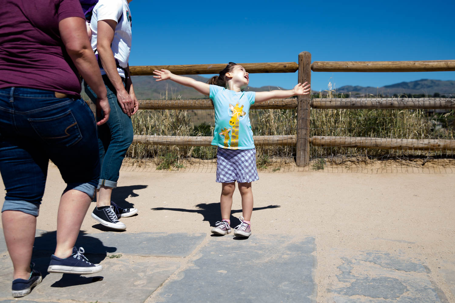 Little girl excited to get to the top of Camelsback Park trailhead overlooking the city of Boise. Waving arms wide and rejoicing.
