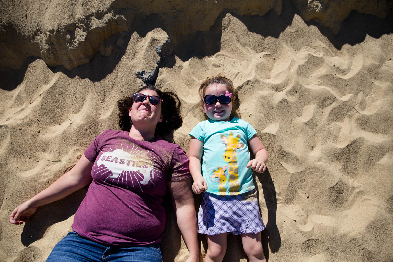 Mom and daughter lying in the sand at Camelsback Park in Boise Idaho during their family photo shoot. Both wearing sunglasses bc the sun is so high and bright. Daughter just threw sand on her mom and mom is squinting.