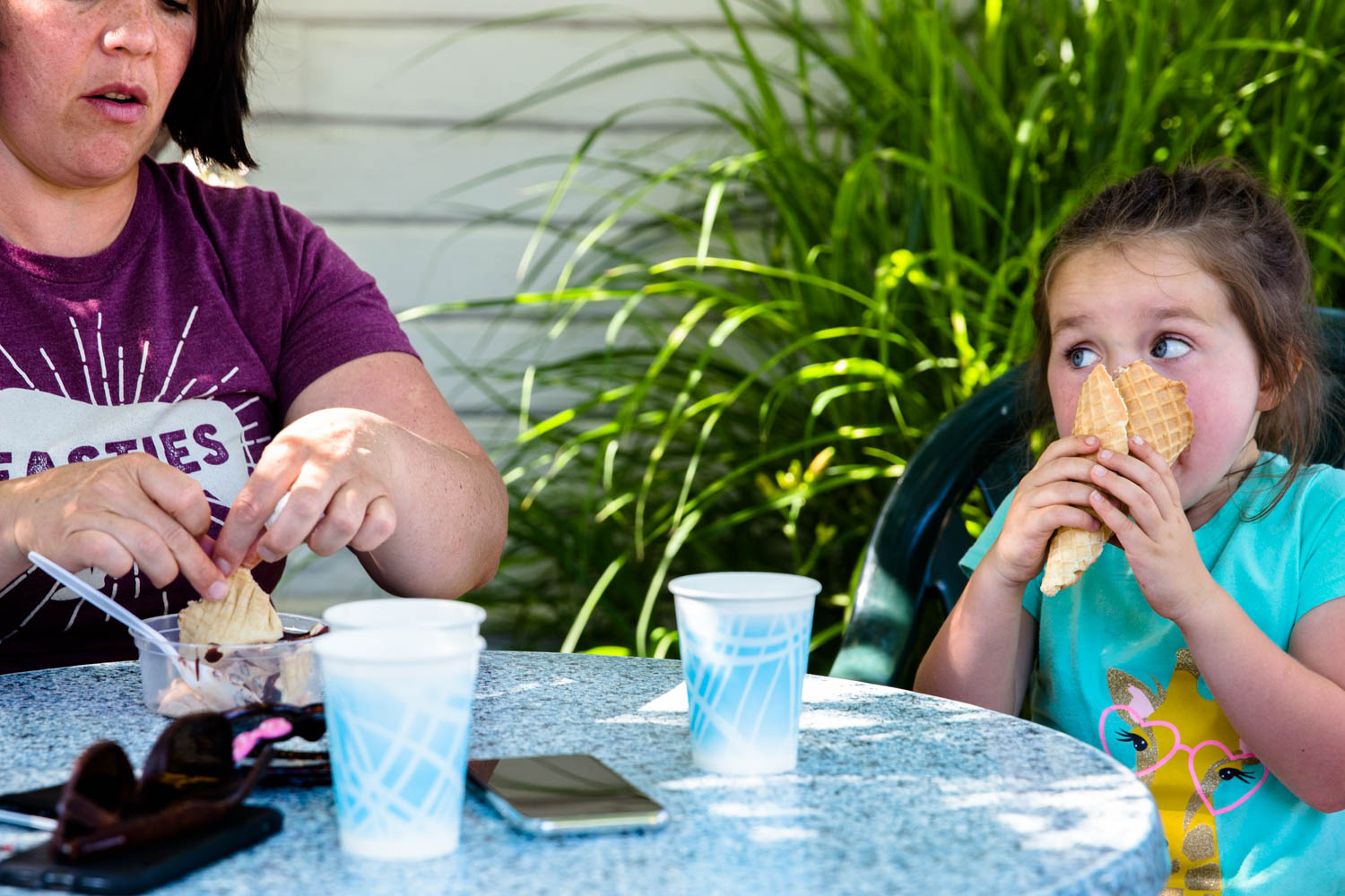 Little girl eating her ice cream ferociously as she sits at the table with mom in hyde park Boise Goody's Soda Fountain
