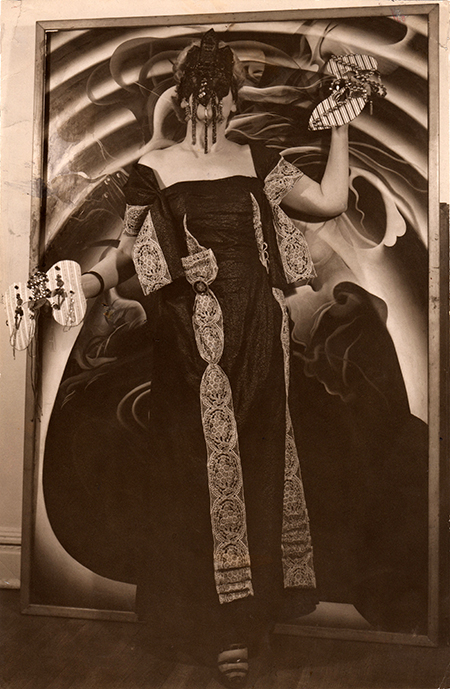 Peavy standing in front of her painting, wearing and holding her masks, circa 1940