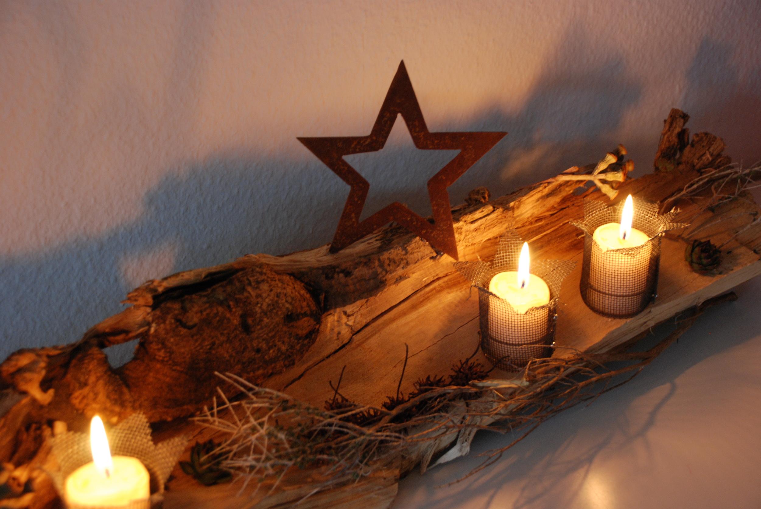 Holzscheit mit Weihnachtsstern und Kerzen