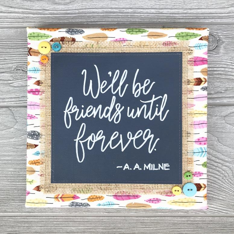 """We'll Be Friends Until Forever - Good friends are some of the greatest joys in life—especially those who are kindred spirits right from the start. This handcrafted artwork is a bright and sunny celebration of all our dear old friends who are always close at heart.10""""x10"""" Handmade Literary ArtworkElements: hand-painted and hand-lettered canvas, colorful burlap, patterned fabric, coordinating buttons, wood frame, claw hangerFeatured Author: A.A. Milne (Winnie the Pooh, 1926)Price: $30 (includes US-based shipping)"""