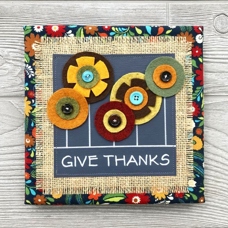 "Give Thanks - Every piece in our floral collection is handmade with love and one of a kind. We combine hand-lettered canvas and hand-cut felt flowers with colorful fabric, burlap and buttons. This unique artwork is sure to brighten your home and your mood!8""x8"" Handmade Literary ArtworkElements: hand-painted and hand-lettered canvas, colorful burlap, ultra-soft felt, patterned fabric, coordinating buttons, wood frame, claw hangerPrice: $25 (includes US-based shipping)"