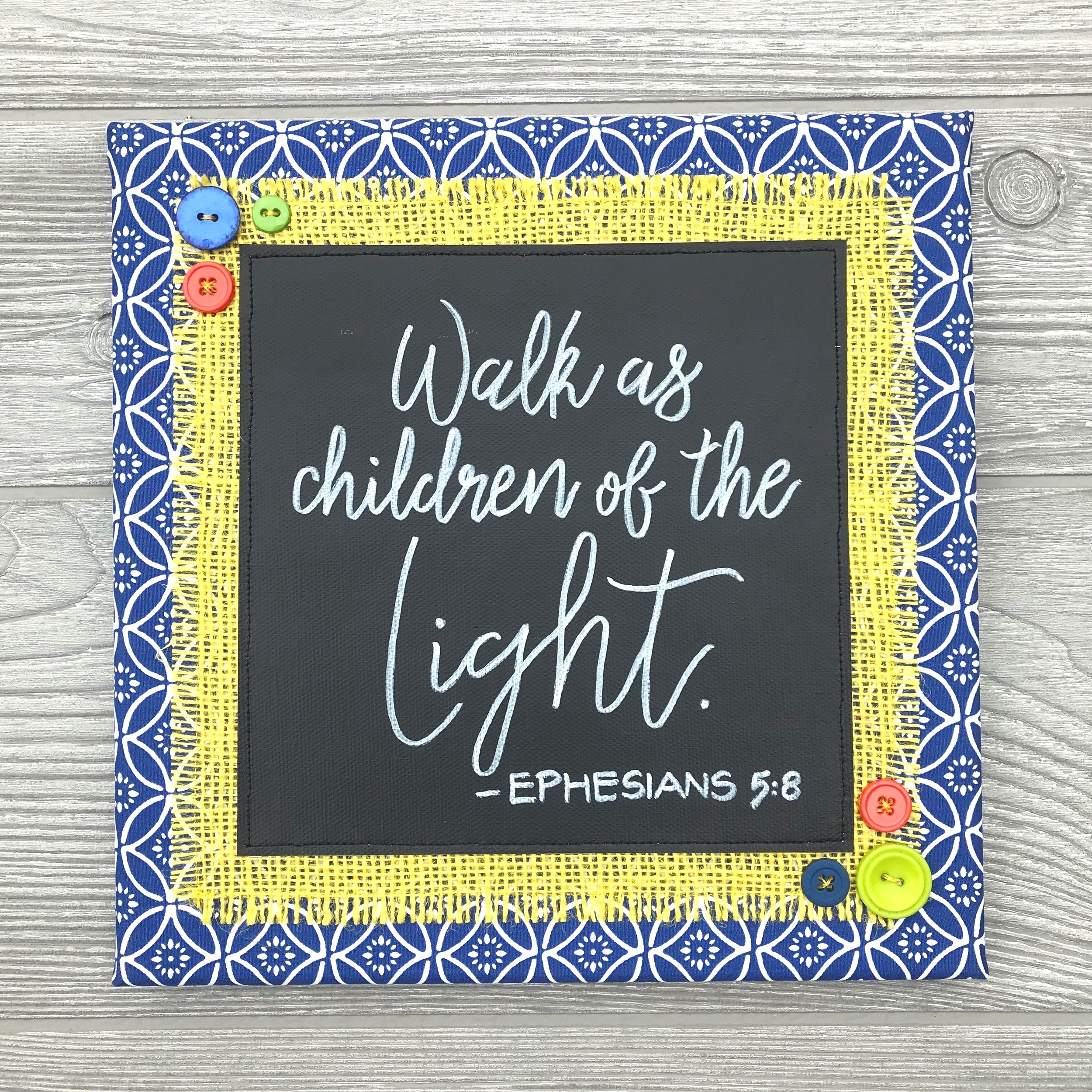 "Walk As Children of the Light - It's no secret that sunshine makes us happy. We crave natural light and the comfort it brings to our souls. This passage from the book of Ephesians reminds us that we should always strive to walk in the light. Isn't that a lovely idea?10""x10"" Handmade ArtworkElements: hand-painted and hand-lettered canvas, colorful burlap, patterned fabric, coordinating buttons, wood frame, claw hangerPrice: $30 (includes US-based shipping)"