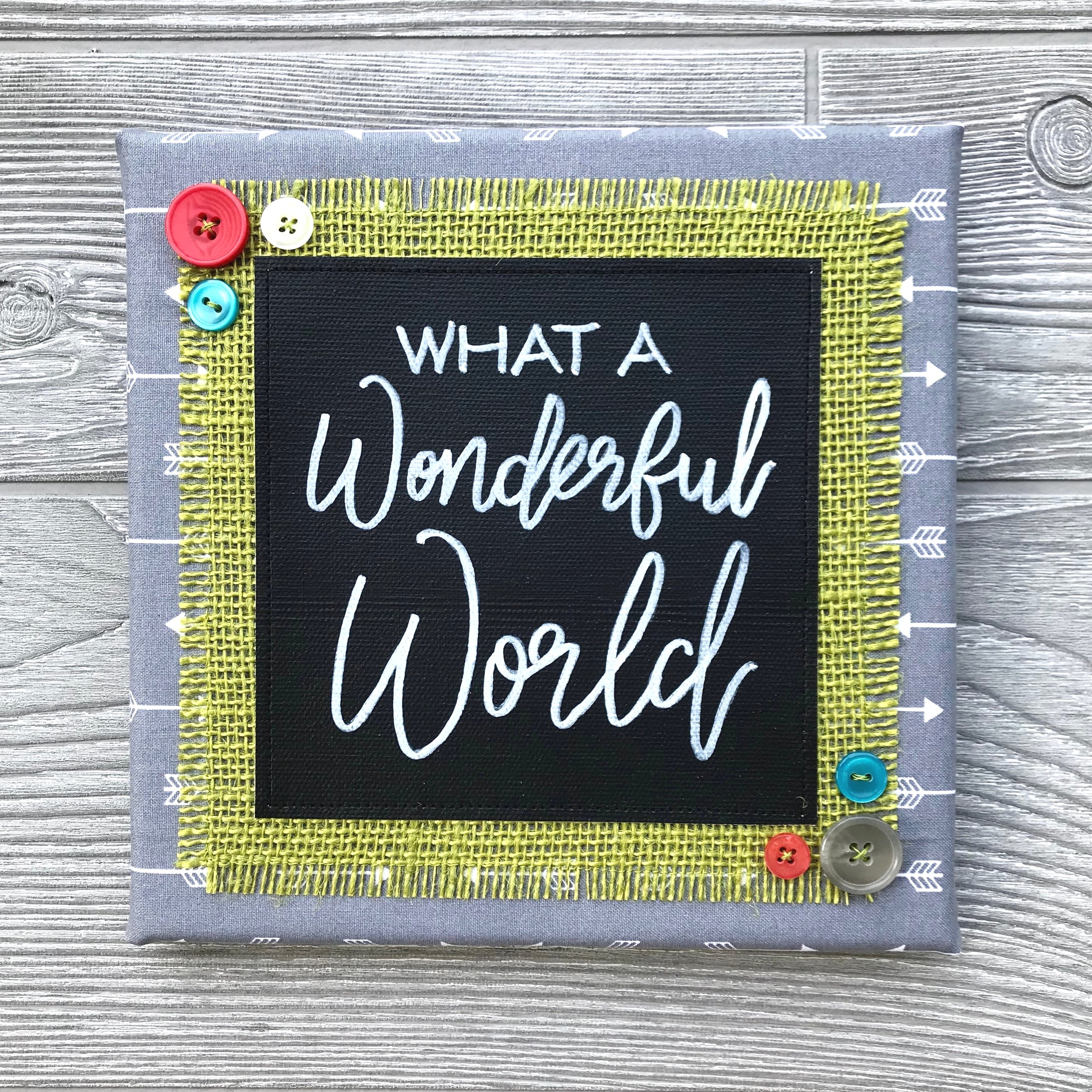 "What a Wonderful World - We live in a crazy, chaotic and often confusing world. But it's a perfectly wonderful world, and we forge perfectly wonderful lives here. Let this artwork remind you of all the good and beautiful things that surround you every day—all the things that make life so sweet!8""x8"" Handmade Literary ArtworkElements: hand-painted and hand-lettered canvas, colorful burlap, patterned fabric, coordinating buttons, wood frame, claw hangerPrice: $25 (includes US-based shipping)"