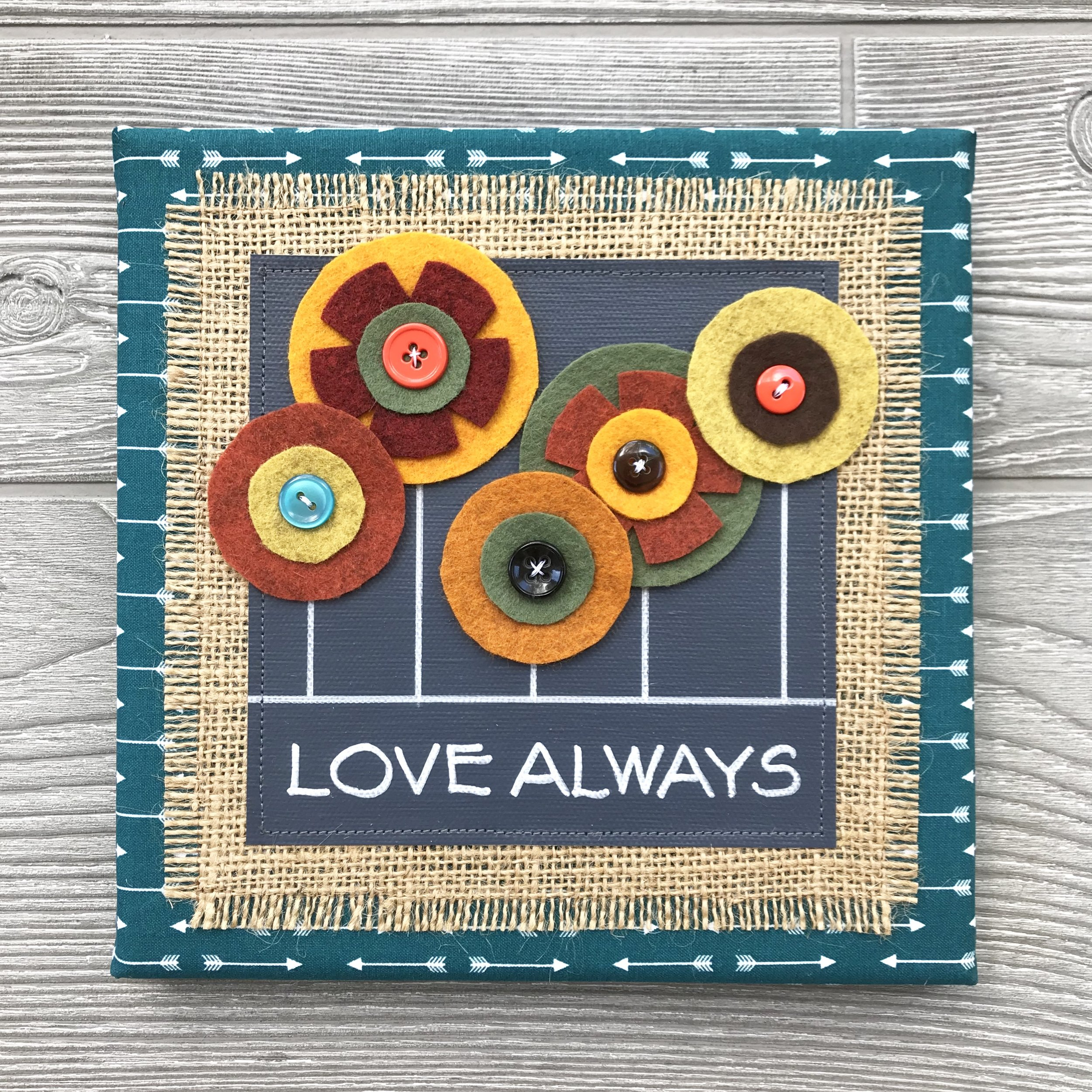 "Love Always - Every piece in our floral collection is handmade with love and one of a kind. We combine hand-lettered canvas and hand-cut felt flowers with colorful fabric, burlap and buttons. This unique artwork is sure to brighten your home and your mood!8""x8"" Handmade Literary ArtworkElements: hand-painted and hand-lettered canvas, colorful burlap, ultra-soft felt, patterned fabric, coordinating buttons, wood frame, claw hangerPrice: $25 (includes US-based shipping)"