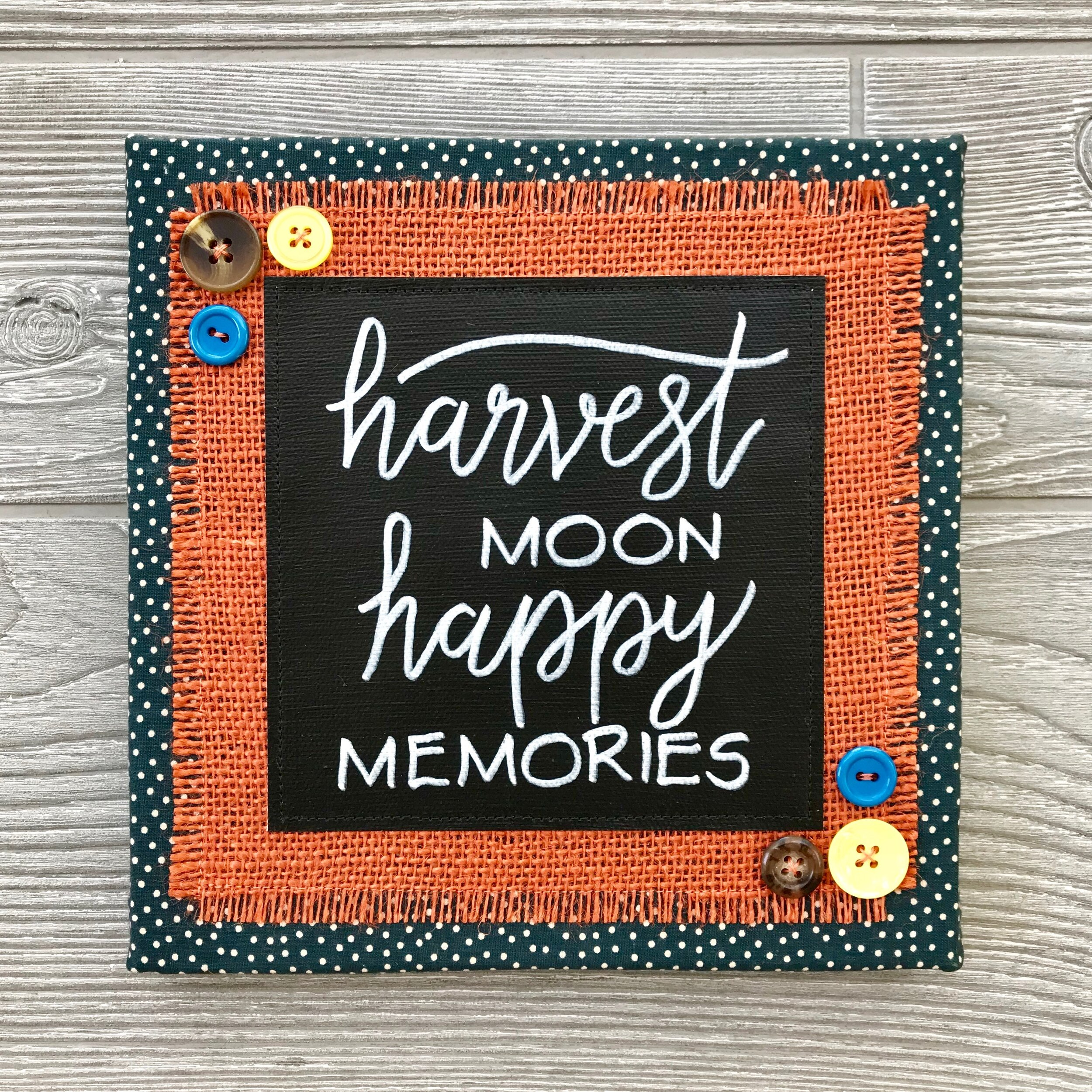 "Harvest Moon Happy Memories - Colorful leaves, warm apple cider, piles of pumpkins...these are the makings of happy memories. May this handcrafted artwork remind you of treasured moments with the people you love.8""x8"" Handmade Literary ArtworkElements: hand-painted and hand-lettered canvas, colorful burlap, patterned fabric, coordinating buttons, wood frame, claw hangerPrice: $25 (includes US-based shipping)"