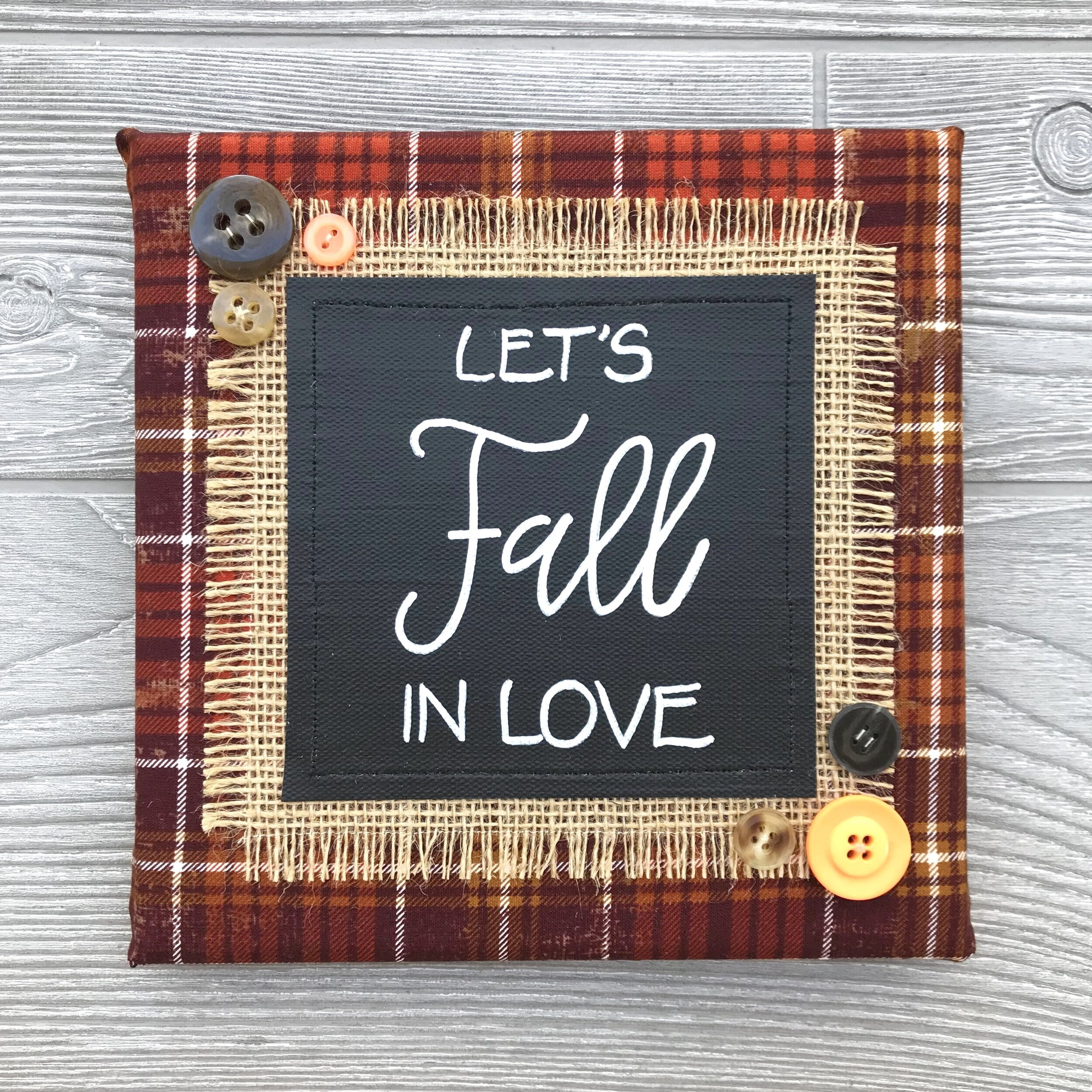 """Let's Fall in Love - Family time at the pumpkin patch...cider donuts and warm cider...cozy sweaters and crisp leaves...there's so much to love at this time of year! Celebrate the season with this handmade artwork—the perfect accent for your harvest home8""""x8"""" Handmade Literary ArtworkElements: hand-painted and hand-lettered canvas, colorful burlap, patterned fabric, coordinating buttons, wood frame, claw hangerPrice: $25 (includes US-based shipping)"""