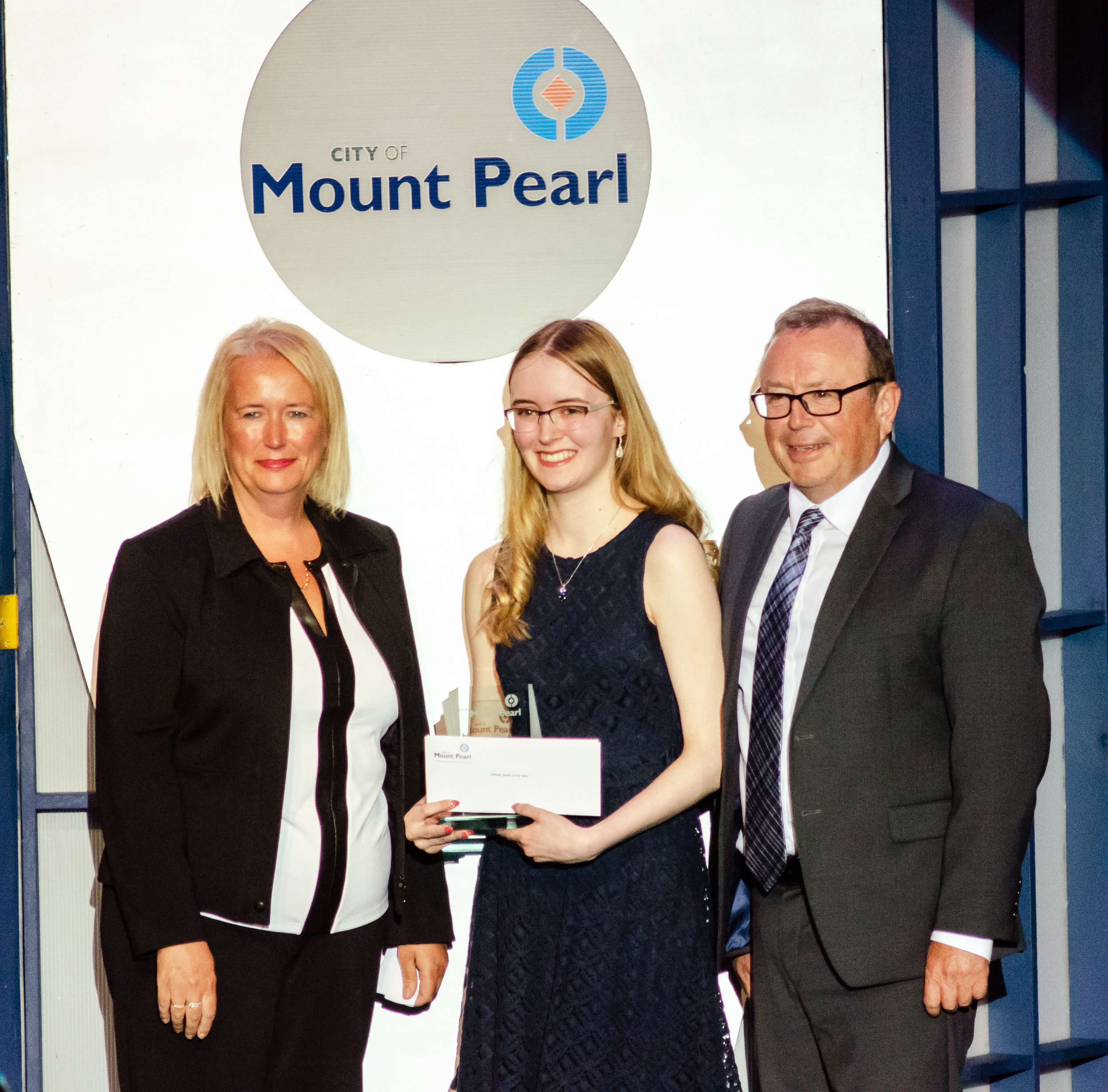Dana Thompson, left, and Mount Pearl Mayor Dave Aker, right, present Youth of the Year Emily Garlie with a plaque at the Focus on Youth Awards held at the Glacier last week. Awards were presented in 16 categories.