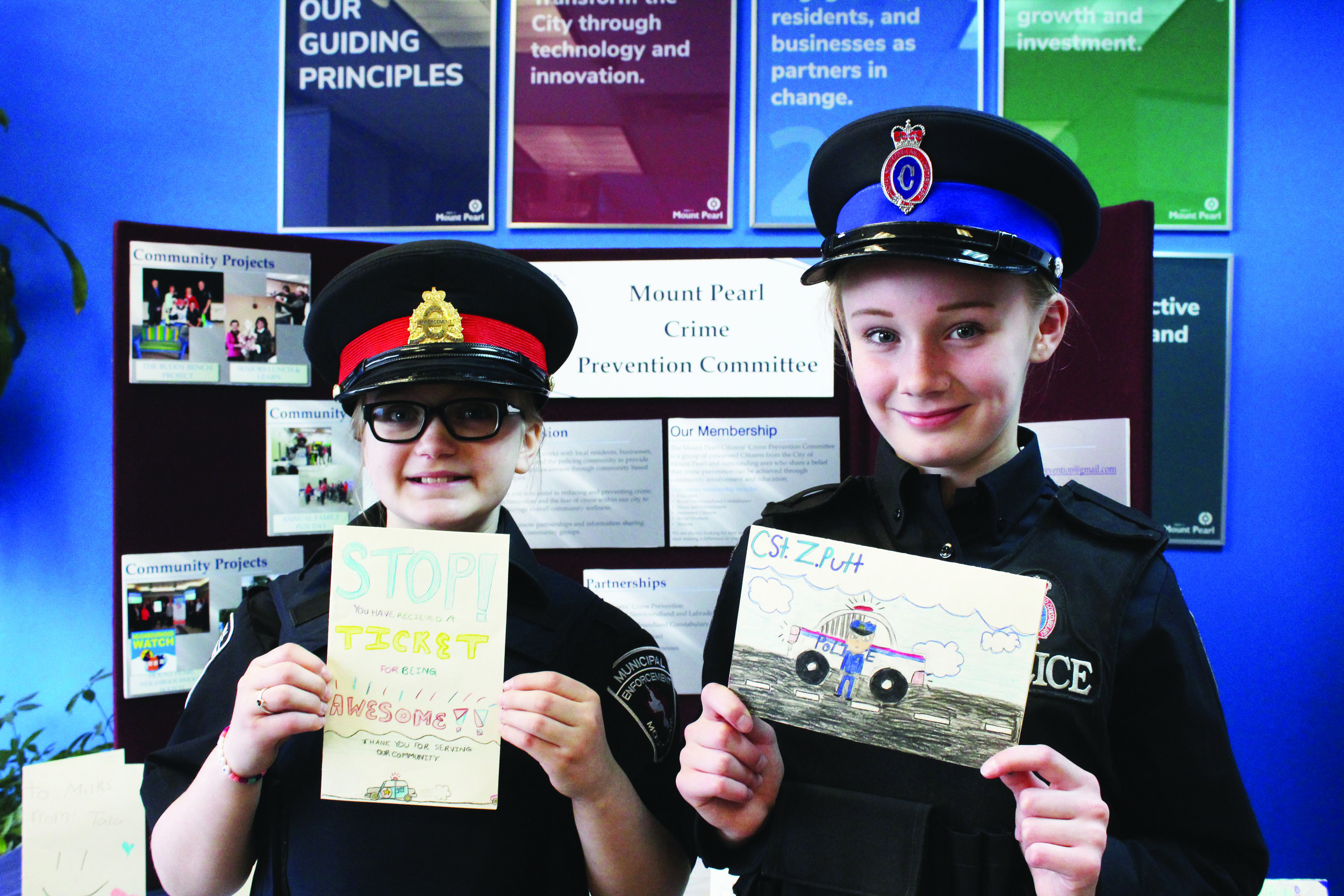 Chloe Valli, left, and Shaylyn O'Keefe were police officers for a day, recently, after winning the right to don badges during an annual celebration of policing by elementary students at Mount Pearl schools.