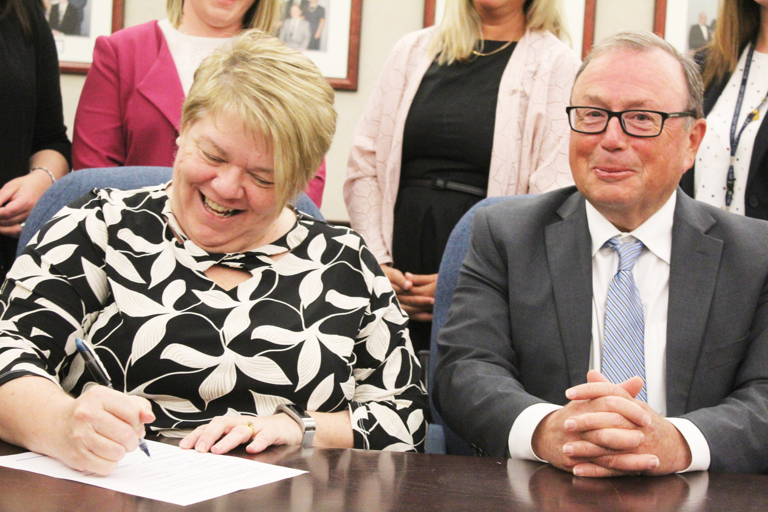 Iris Kirby House executive director Michelle Greene signs the memorandum with Mount Pearl mayor Dave Aker.