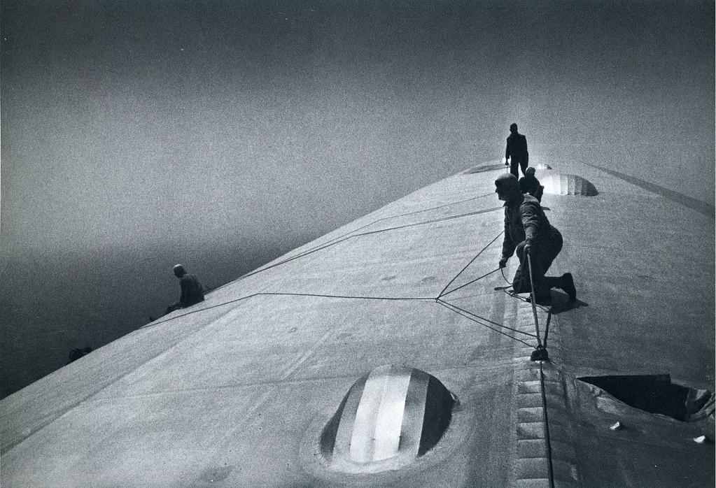 Mechanics fixing hull of a blimp inflight over the Atlantic (1934) - Some things need fixing while the project runs!