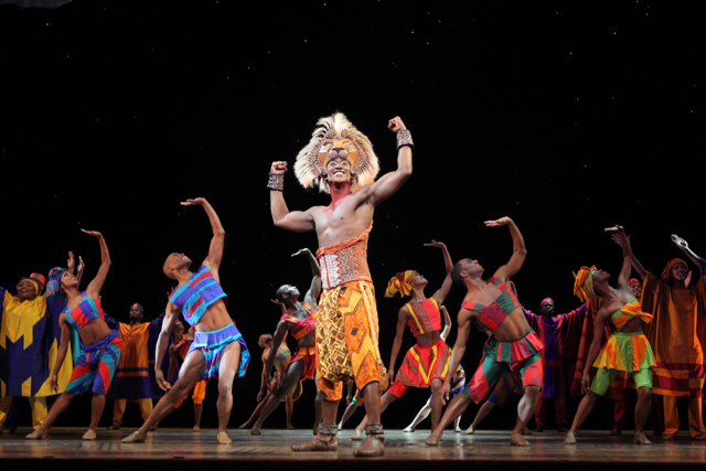 "Aaron Nelson (centre) leads the company of ""The Lion King"" in the role of Simba. Photo by Broadway Across Canada."