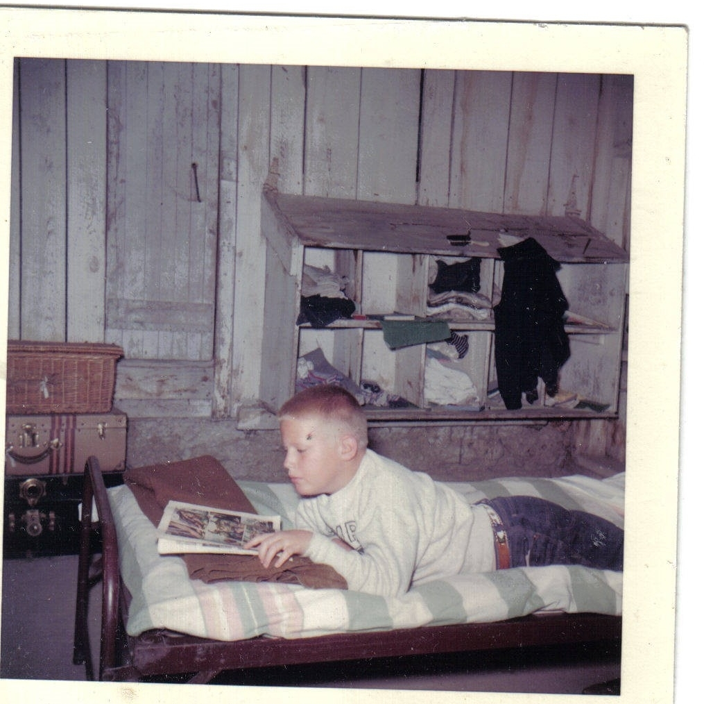 ca. 1959:  Rest hour in the old boys' bunkhouse, (a renovated chicken house – note the nesting boxes converted into cubbys)  By the way, this camper is now the parent of three JE former campers and staff members:  Nate, Sam and Molly Sherwood.