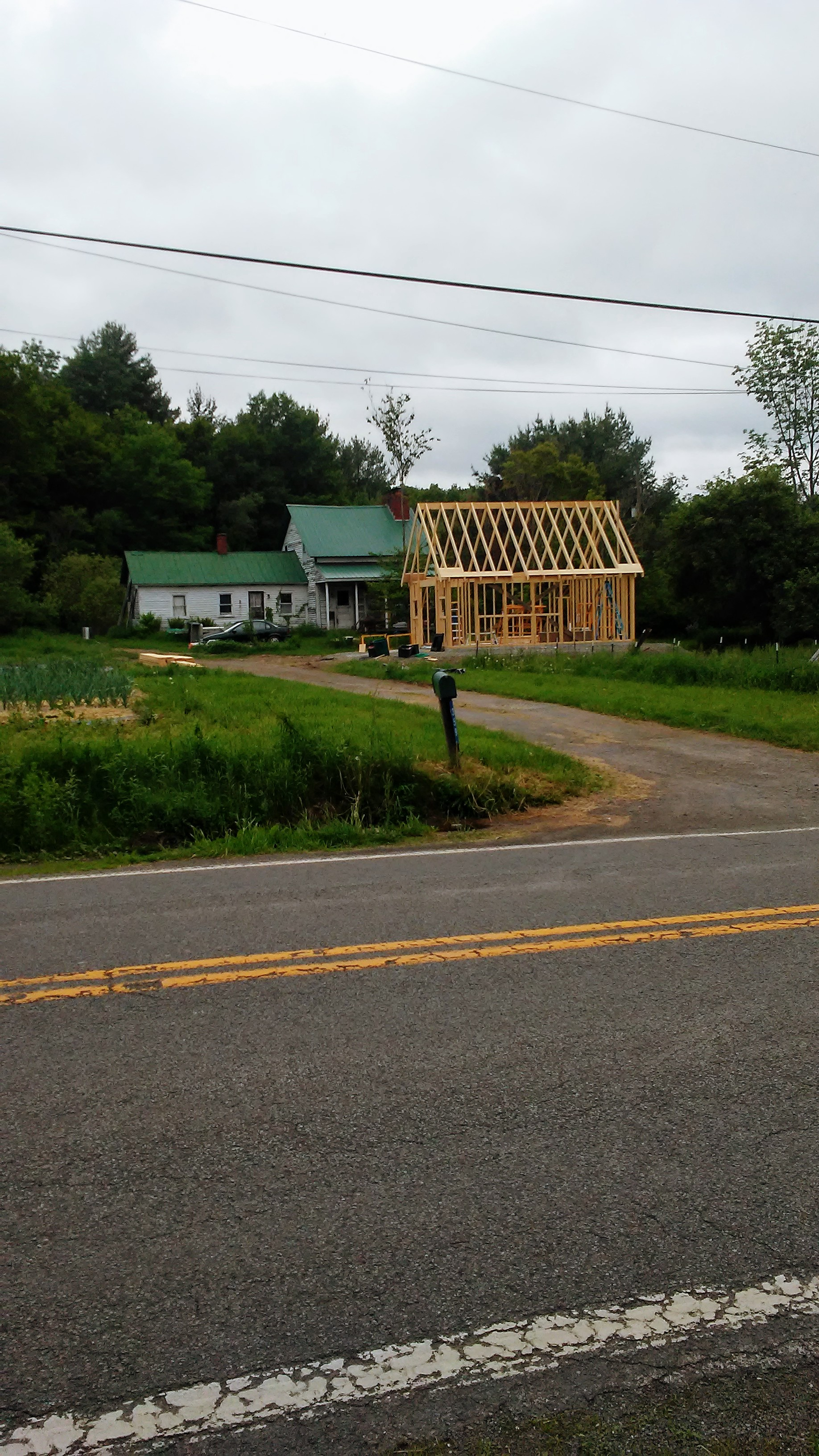 Here's the view from across the road, with Milt's house in the background. The ability to store vegetables in the walk-in and prep for market under a roof on rainy days makes us farmers jump for joy!