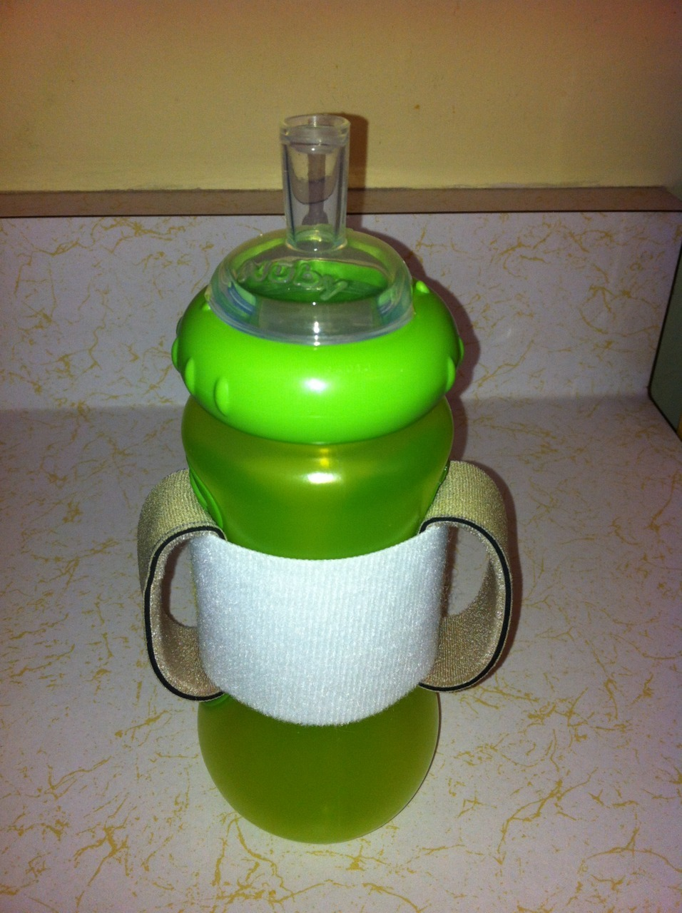 "This is an adaptive handle that I made to put on a sippy cup, in order to facilitate holding the cup or working on bringing cup to mouth. I used Velcro Easystrap around the base, as it is easily adjustable and could be used on various sized cups. The ""handles"" are made of Neoloop, which is essentially a neoprene material. It has a stretch to it, which allows the hands to slide in and remain secure against the cup. None of it is sewn together to allow adjustability."