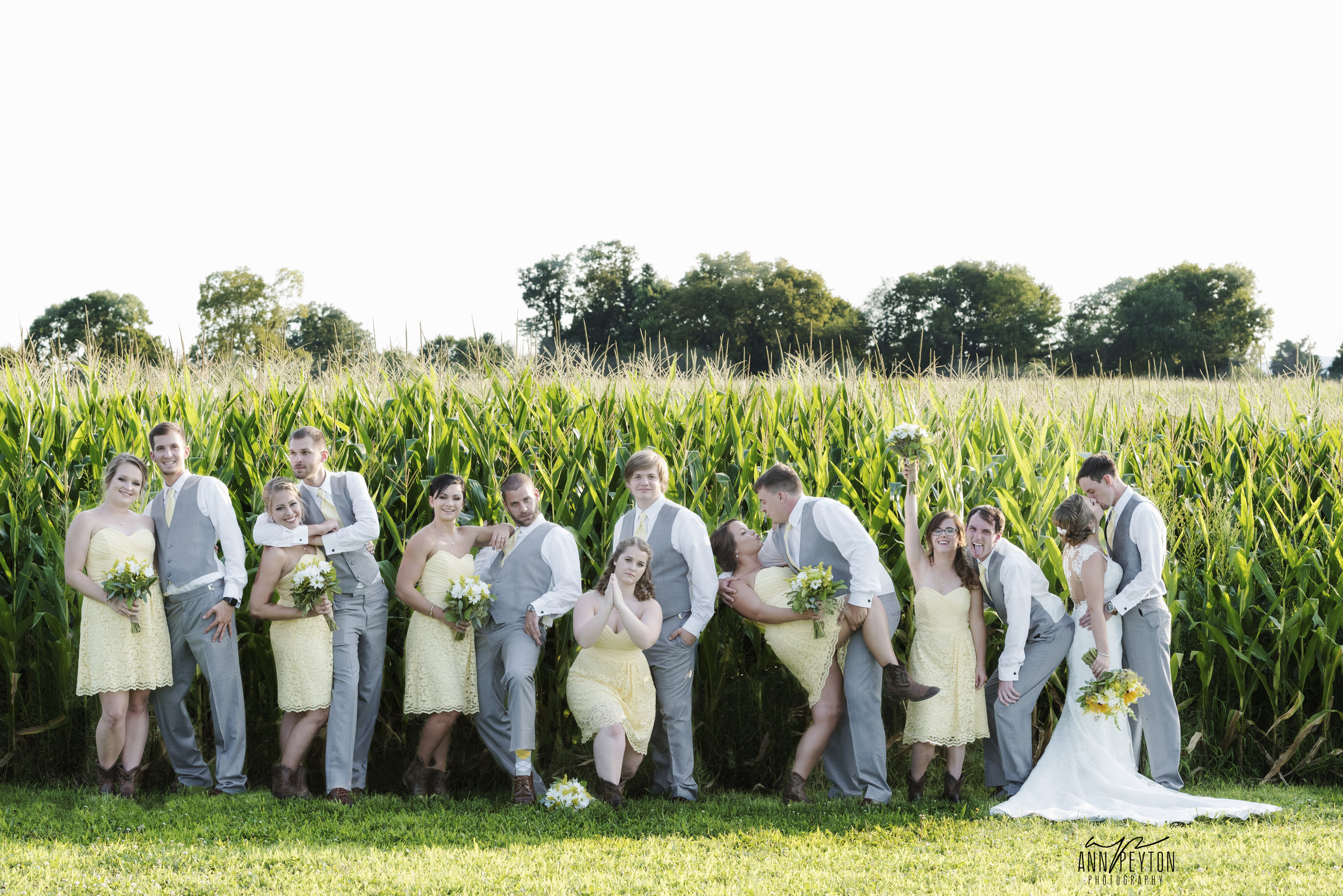 Britany and Travis with bridal party by cornfield fun pose