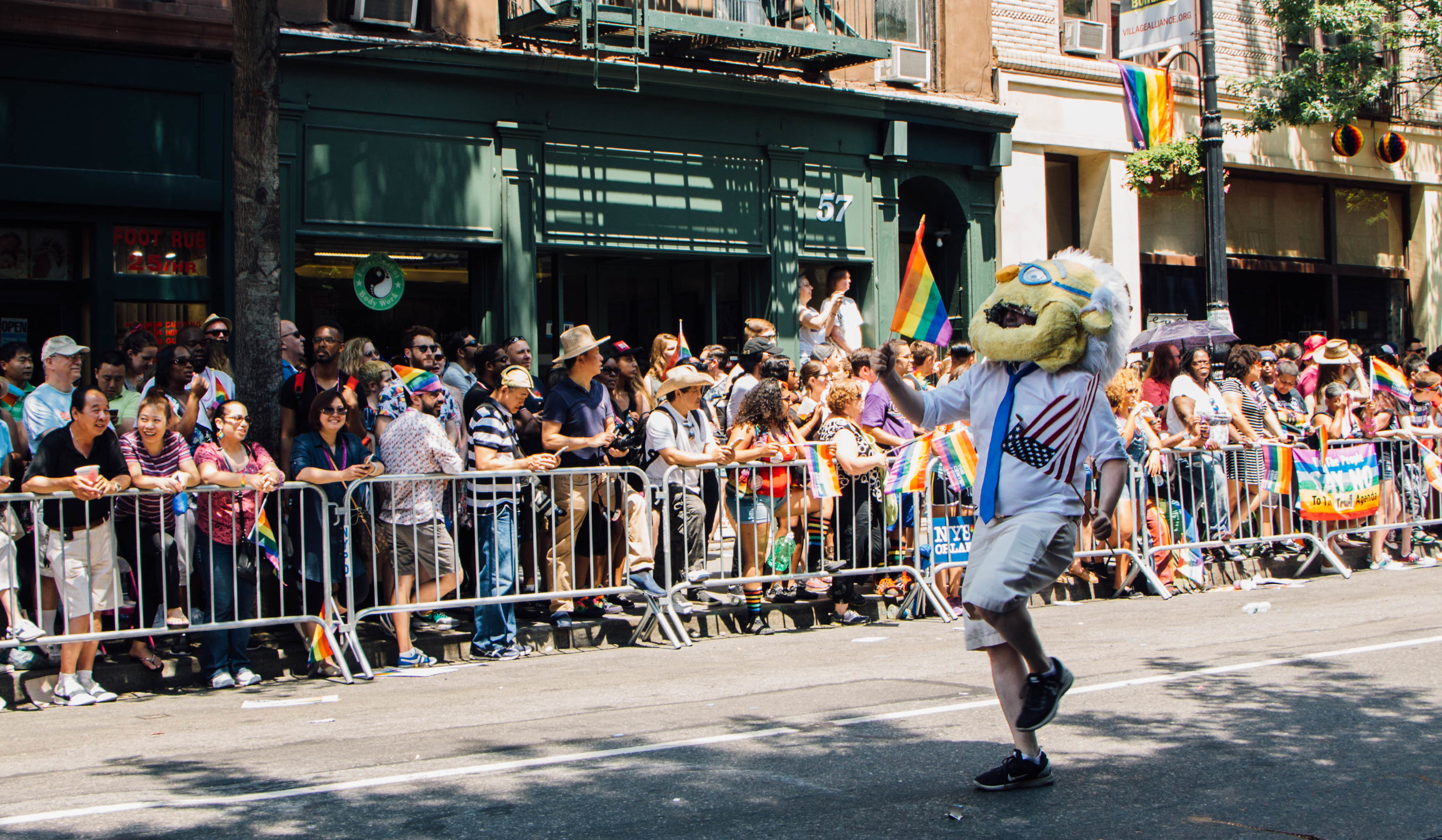 A Bernie Sanders mascot parades down 5th Avenue.