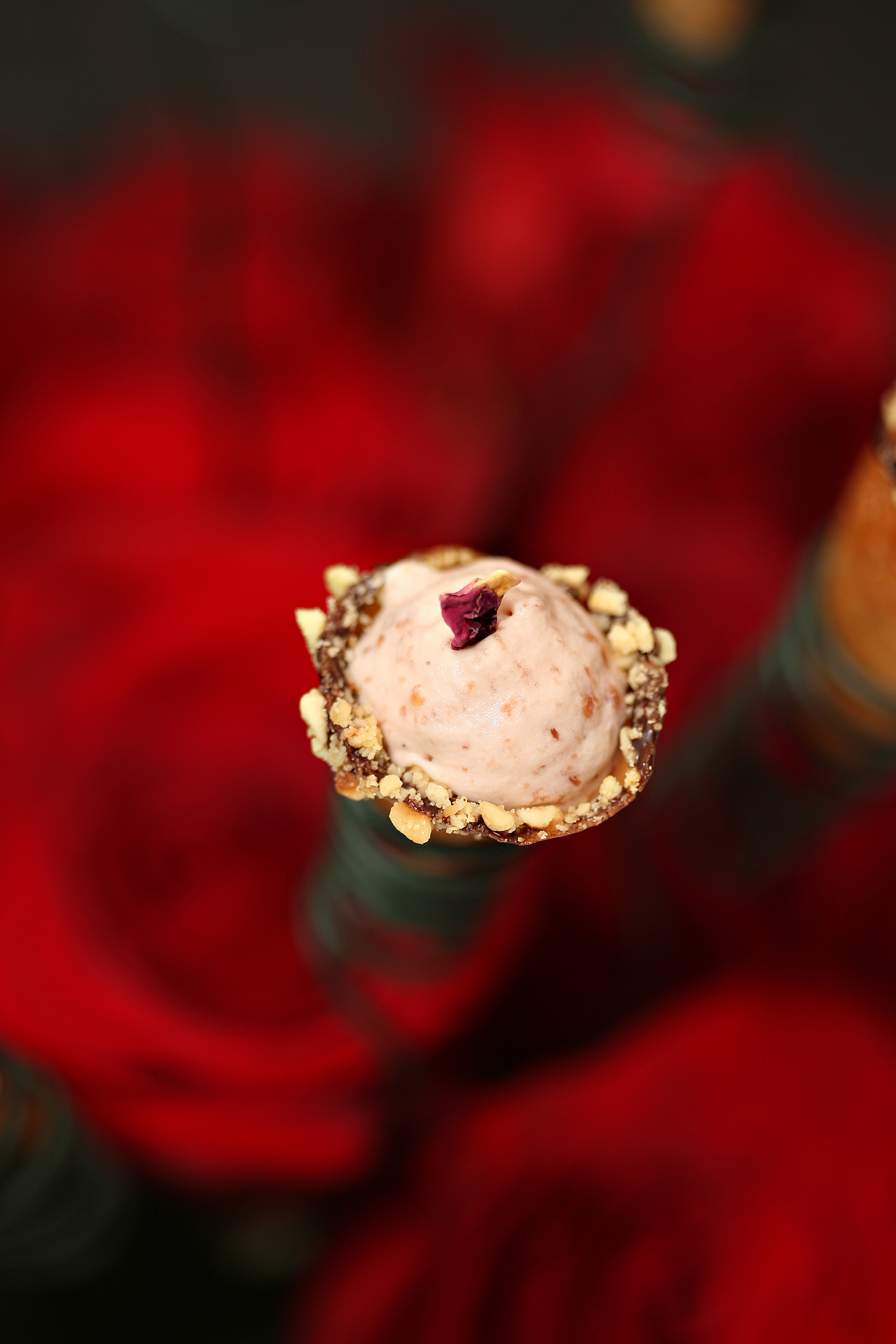 Rose ice cream with hazelnut edges cornets served in abowl of roses