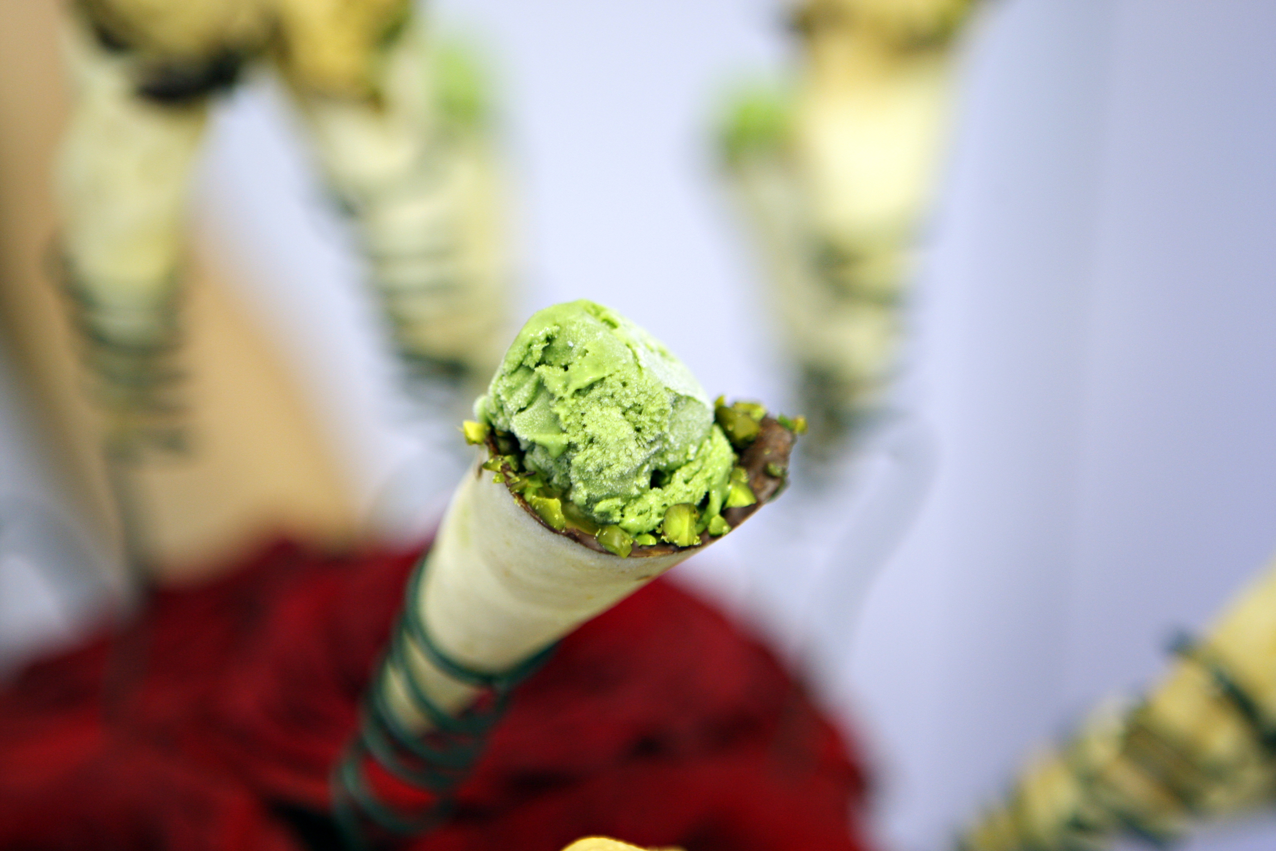 Pistachio ice cream with pistachio edged cones served in a bowl of flowers