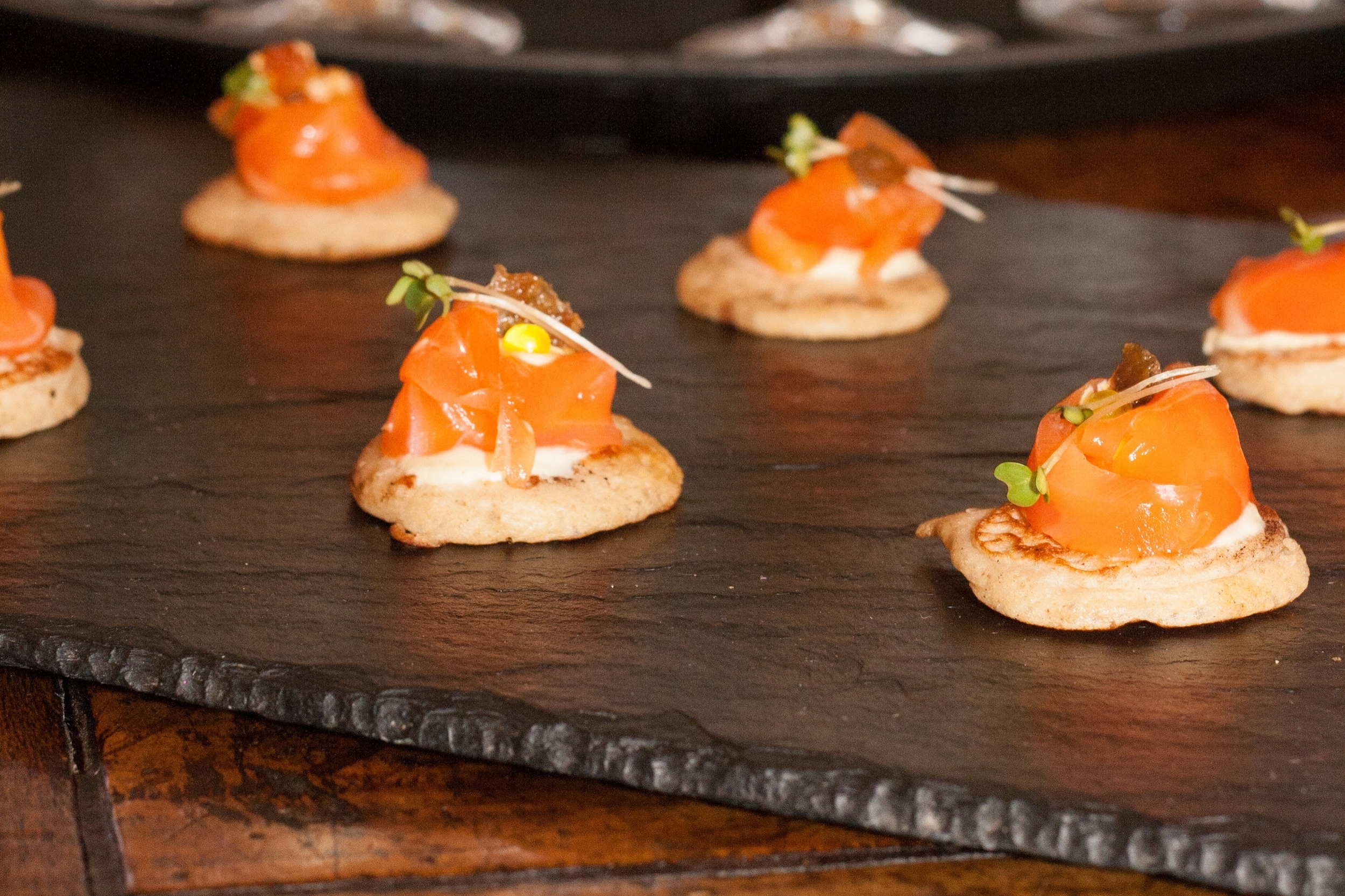 Citrus cured salmon on a sweet potato blini with lime pickle creme fraiche