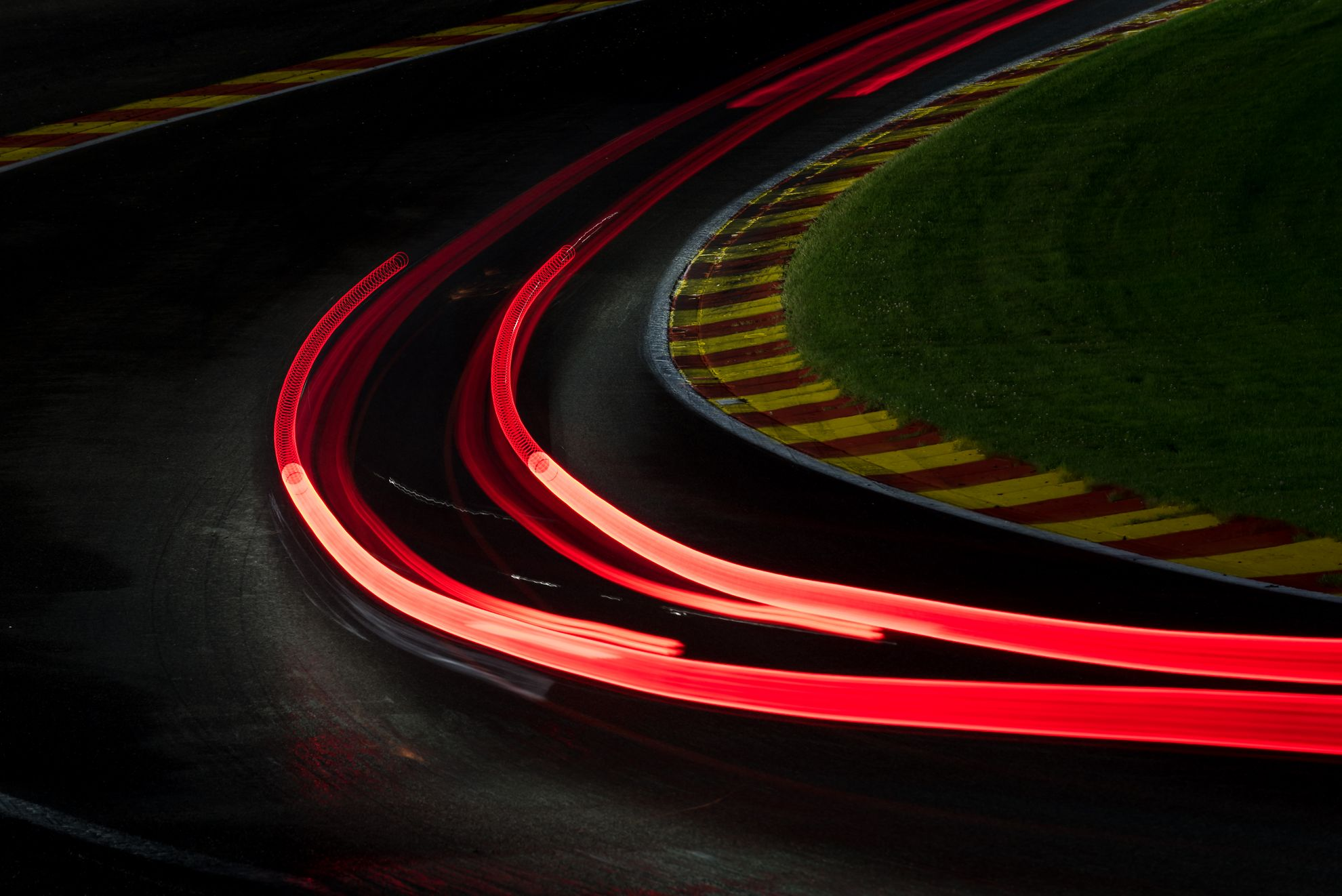The cars pushing hard through Eau Rouge during the night.