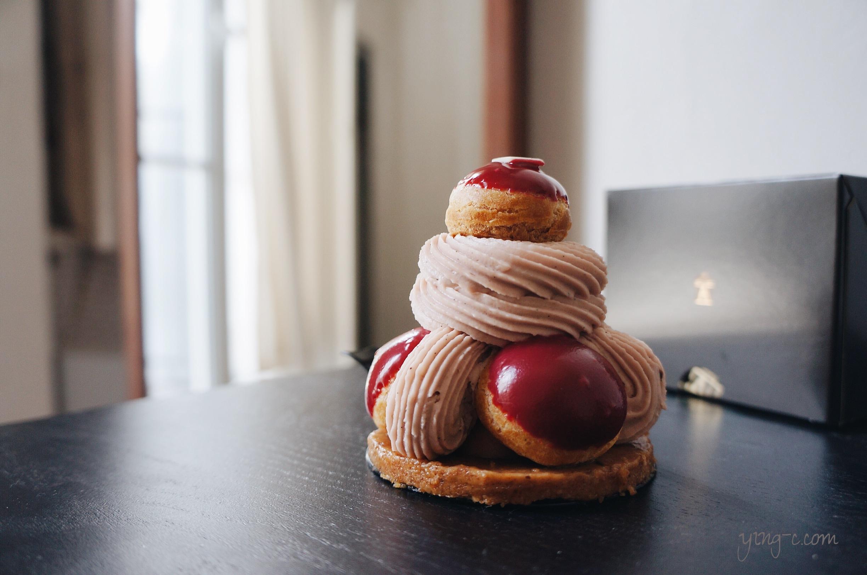 圖2:巴黎甜點店  Angelina  的 St. Honoré 「 Désiré 」,是由底部的花生醬奶酥脆片(croustillant crumble)取代傳統的千層派皮,再加上泡芙、草莓奶醬夾心(coeur crémeux à la fraise)、覆盆子香緹鮮奶油(Chantilly à la framboise)、泡芙上的翻糖裝飾與頂部的一片造型白巧克力構成。(攝影:Ying Chen)
