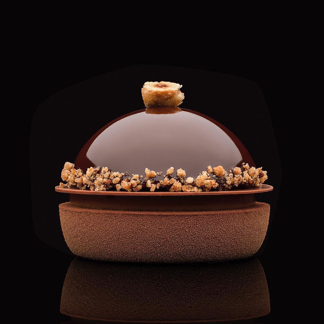知名甜點主廚  Claire Heitzler  為  Ladurée  設計的巧克力榛果蛋糕「Le Savoureux」,上下兩層分別以鏡面淋醬和空氣噴槍法覆蓋表面、半球形的慕斯底部以榛果碎圍邊、頂端也用榛果裝飾。 Photo|Instagram  @antoninbonnetphotography