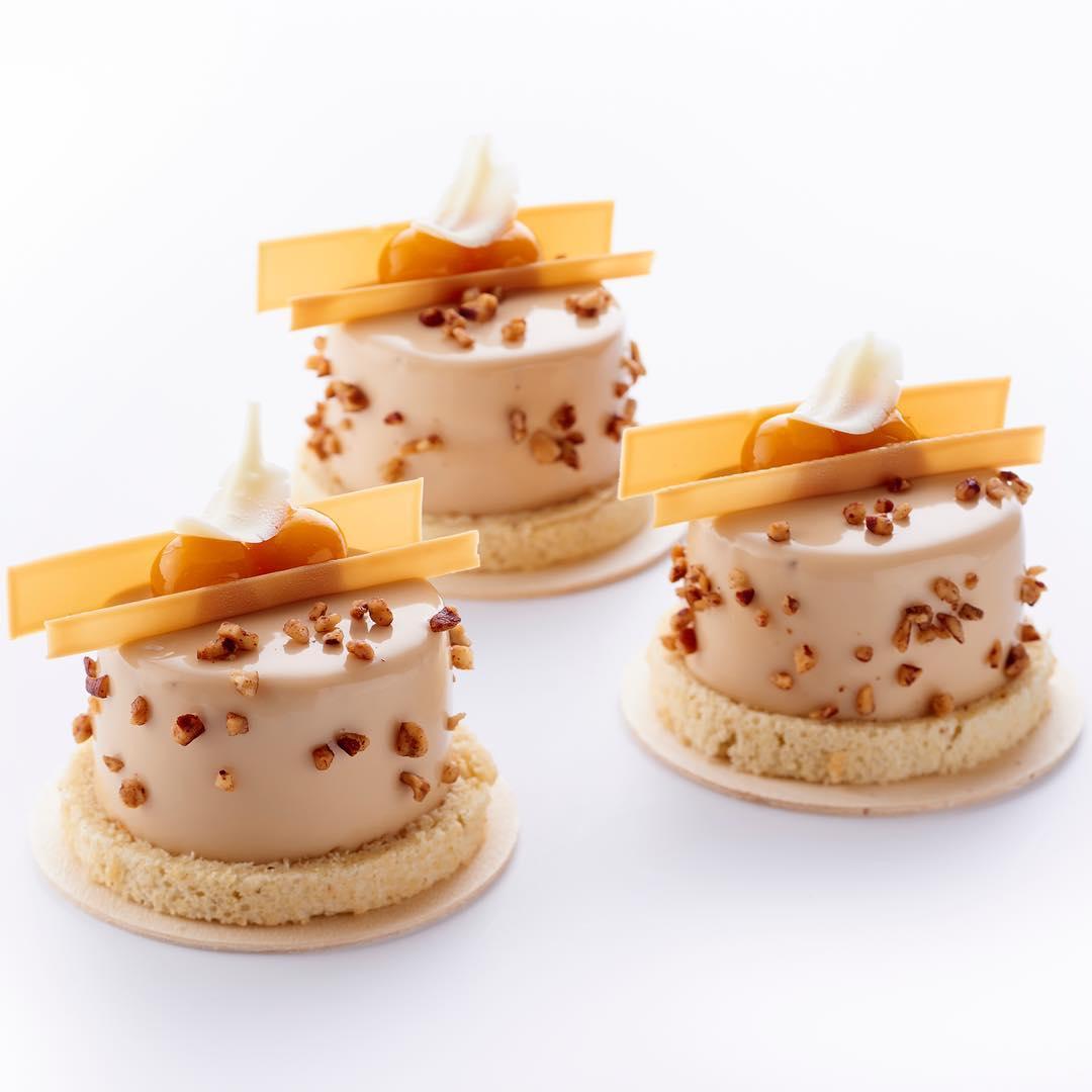巴黎  Park Hyatte Paris-Vendôme  飯店的甜點主廚  Jimmy Mornet  創作的「entremet noix de pécan & fruits de la passion」(核桃與百香果蛋糕)。蛋糕的淋面與裝飾不管是色彩還是元素,皆完整呼應主成份核桃與百香果。 Photo|Instagram  @jimmy_mornet