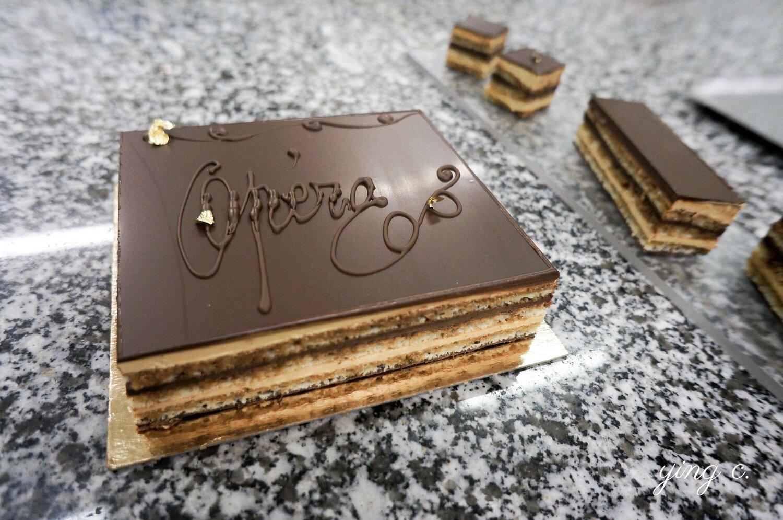 法式經典「Opéra」歌劇院蛋糕,由 biscuit joconde(法式杏仁海綿蛋糕)、crème au beurre café(咖啡奶油霜)、ganache chocolat(巧克力甘納許)組成,三種元素依序堆疊起來後,還要再加上 glaçage chocolat noir(黑巧克力淋面)與裝飾才算完工。