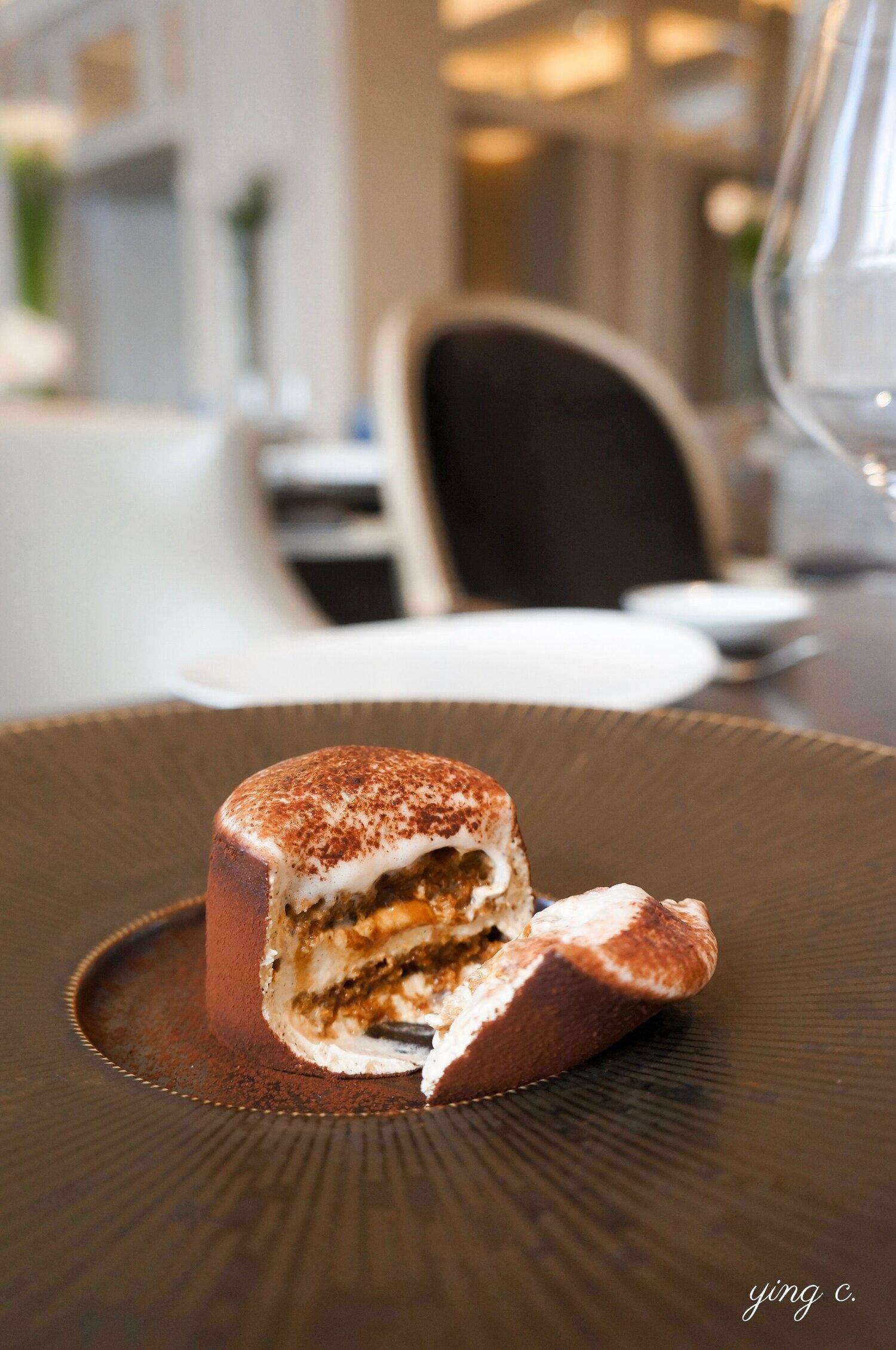 Maxime Frédéric  主廚為  Le George  義式餐廳創作的提拉米蘇,從切面中可以清楚地看見它的結構,包含 biscuit l'Annécien(Annécien 海綿蛋糕薄片)、crème tiramisu(提拉米蘇奶餡)、glace café à froid et lait infusé(冷泡咖啡冰淇淋)、crispy sarrasin(酥脆蕎麥)、mousse de lait(牛奶慕斯)等,再以諾曼地新鮮白乳酪製成外環包裹。  這也是一道用典型的法式蛋糕組成邏輯去重新演繹異國經典的作品: 麵糰 (Annécien 海綿蛋糕薄片,另外再加酥脆蕎麥增添口感)+ 奶餡 (提拉米蘇奶餡、咖啡冰淇淋)+ 裝飾 (牛奶慕斯、可可粉)。本蛋糕沒有淋面,但是由諾曼地新鮮白乳酪外環裹住全部的層次、再灑上可可粉,取代了淋面的作用。一人份小蛋糕的形式,比原始版本更為精緻。