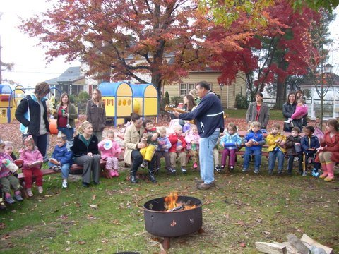 School get togethers include singing in front of a camp fire