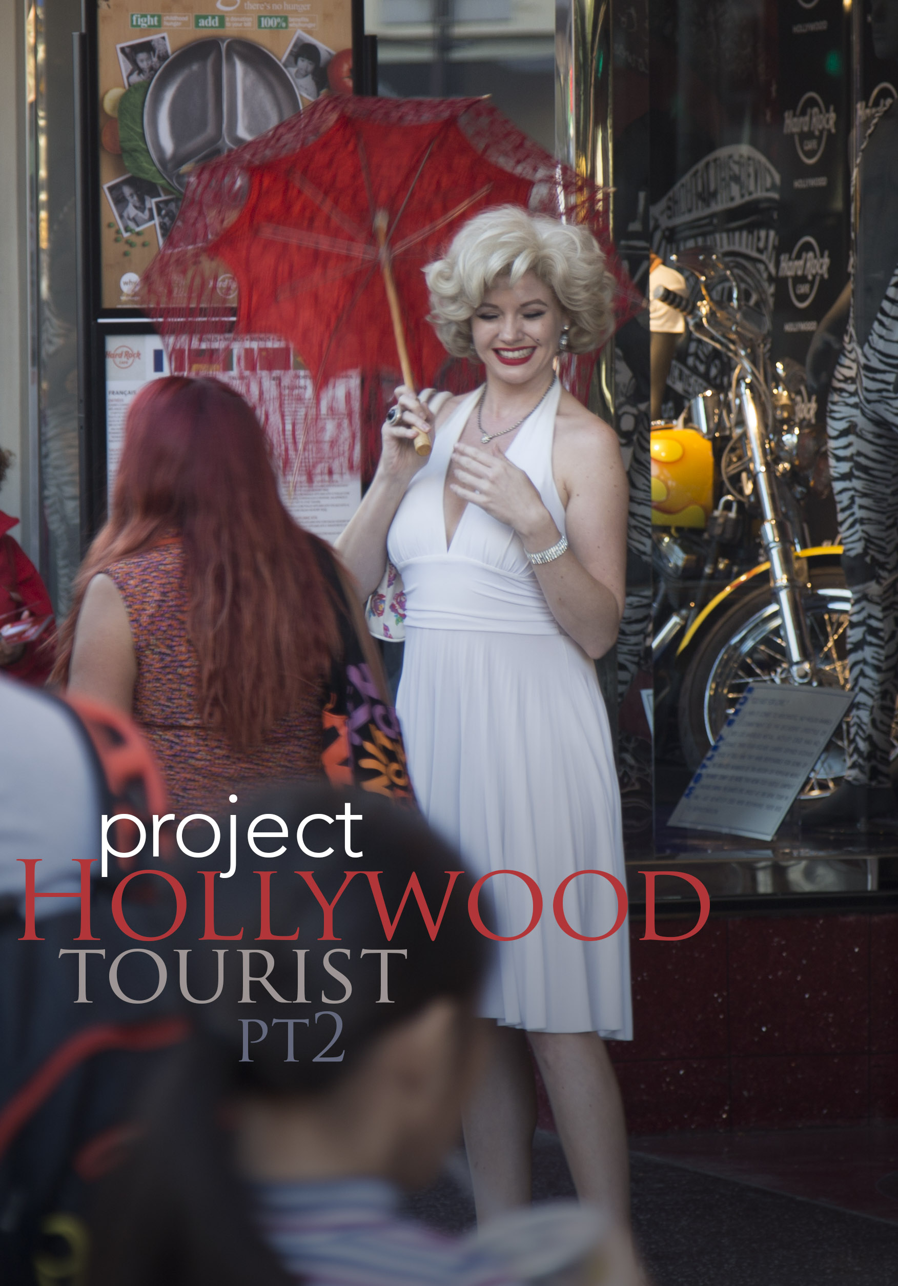 A Marilyn Monroe impersonator poses with tourists on Hollywood Blvd for $$