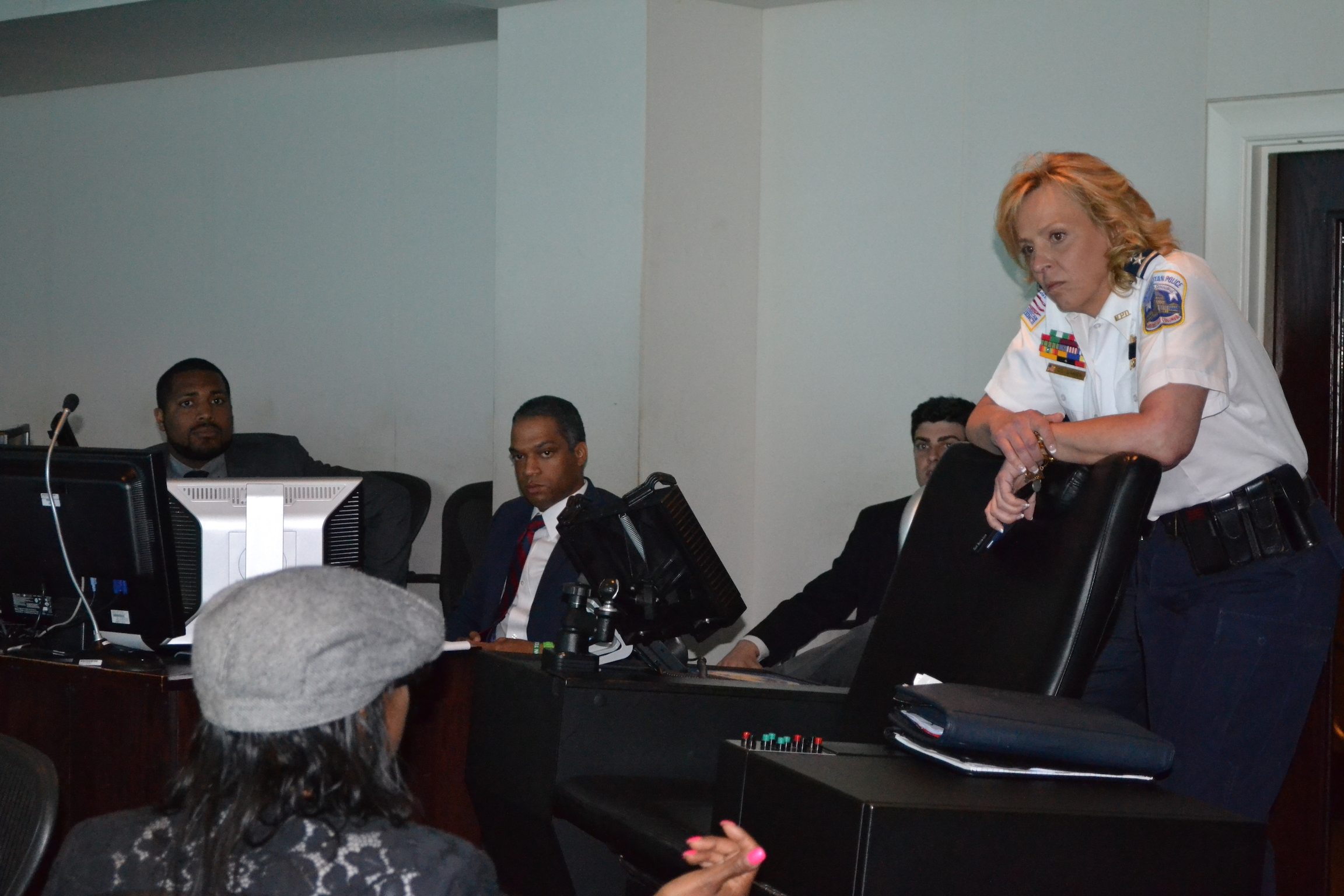 Chief Cathy Lanier listening to a resident. Far left is Gregory Jackson, director of the Mayor's Office of Community Relations, and Councilmember-Elect Brandon Todd.