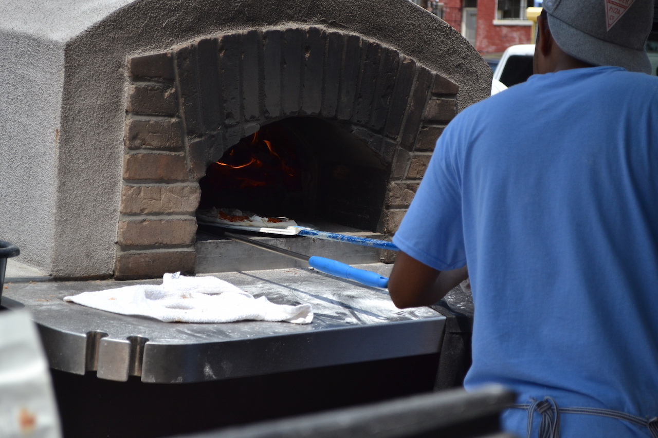 The pizza going into the brick oven
