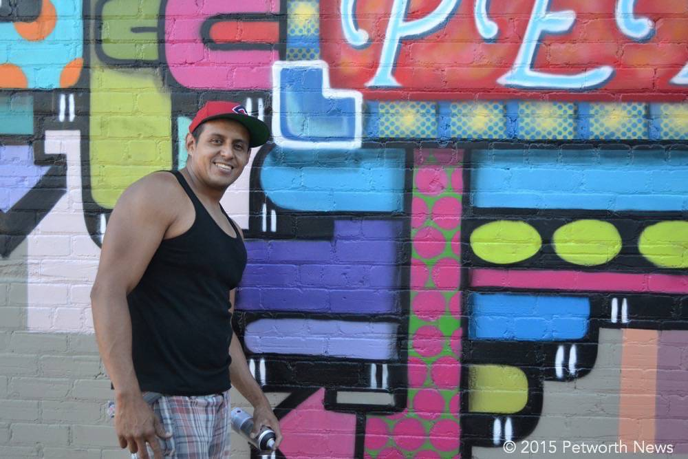 Artist Juan Pineda poses next to the almost-finished mural.