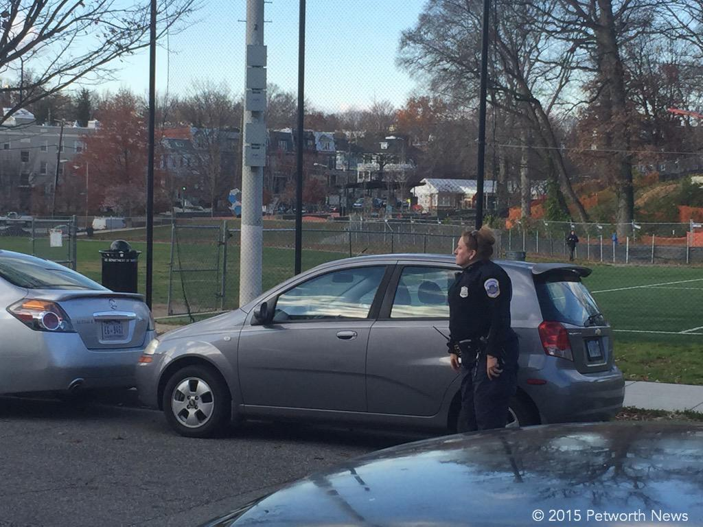 An MPD officer shooing away double-parkers on Thursday, Dec 3rd.