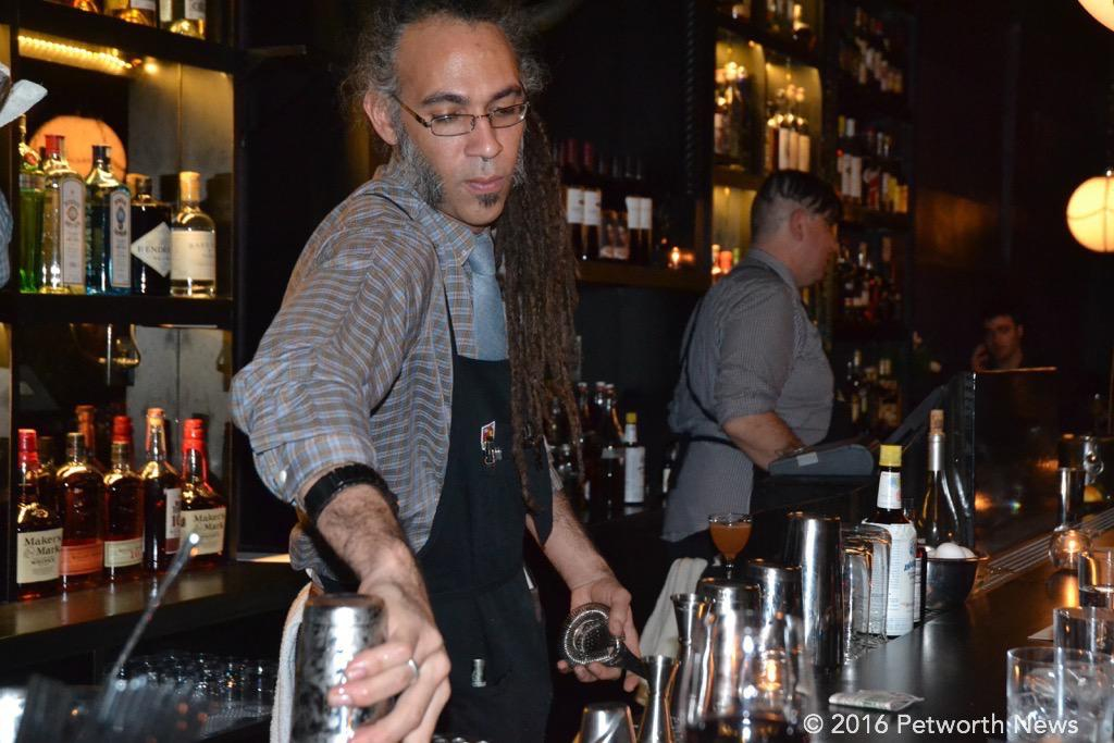 Calvin about to mix another drink, while Burke just served a customer.