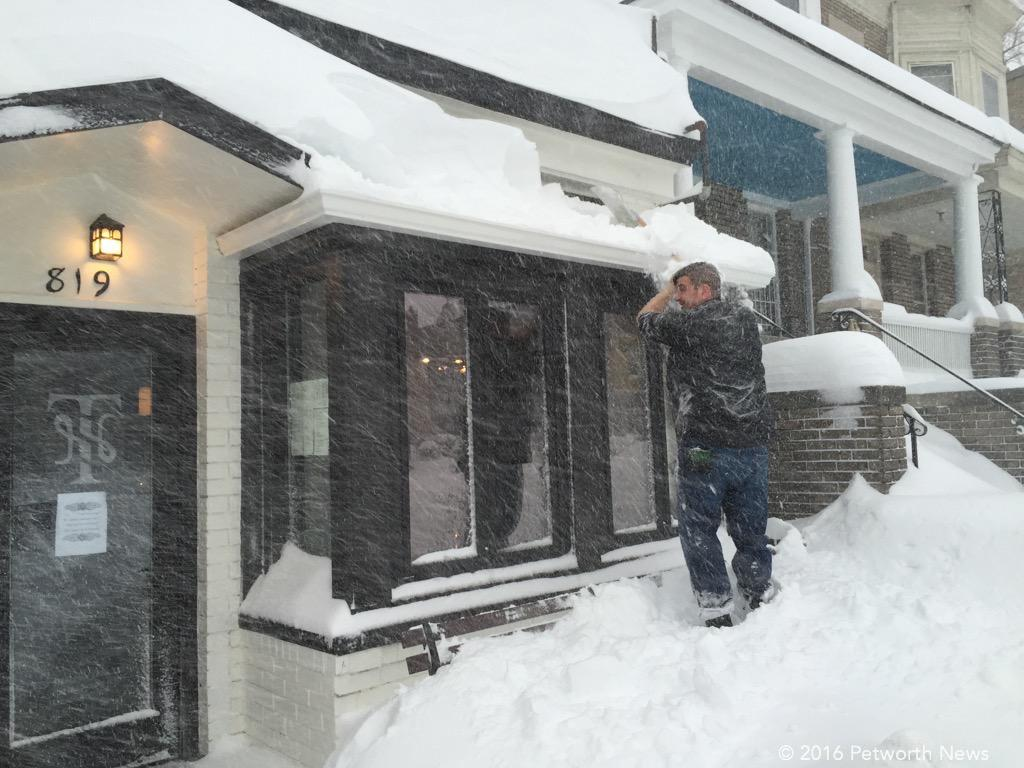 Burke Podany from Twisted Horn, cleaning the awning (they are open all weekend until 1:30am)