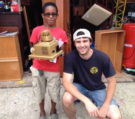Noah buying an old projector from a young customer. (Courtesy Noah David)
