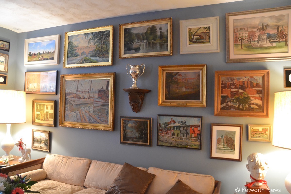 The living room in Kent and Brian's house is covered with paintings from around DC.