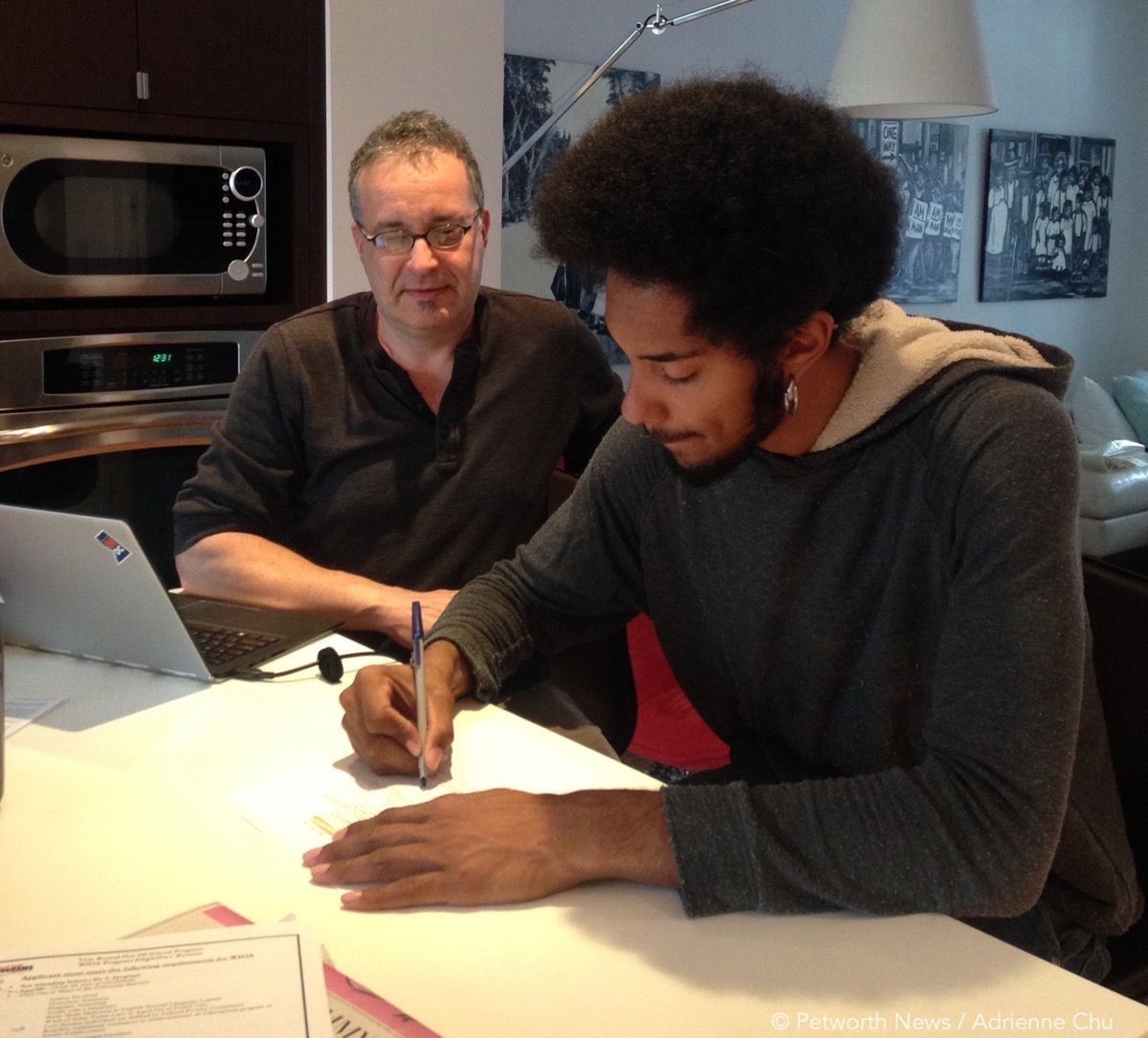 David Sheon, founder of DC Community Carrot, helps Colin Clarke fill out the application for the nonprofit's entrepreneurship program.