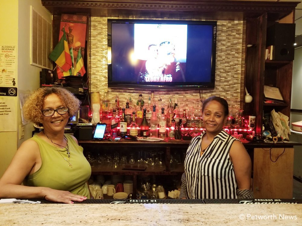 Mignot owner Sinafkish Asefa (left) poses behind the bar with waitress  Almaz Tessema .