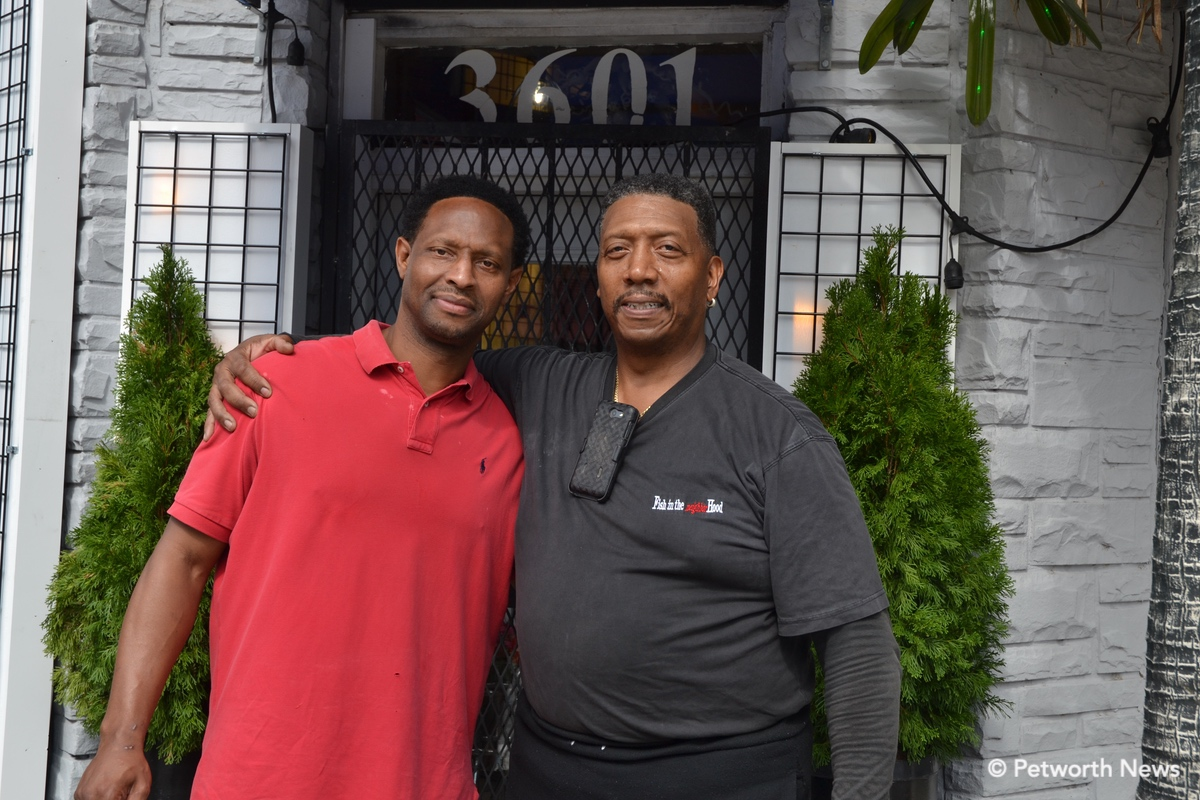 Santana Shabazz poses with Bill White, owner of Fish in the Neighborhood.