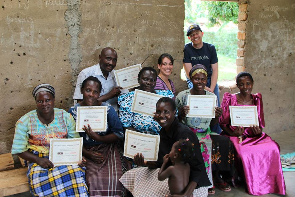 Amanda and Benjamin with their students in Uganda, holding certificates from completing classes from Lovin' Soap Project.