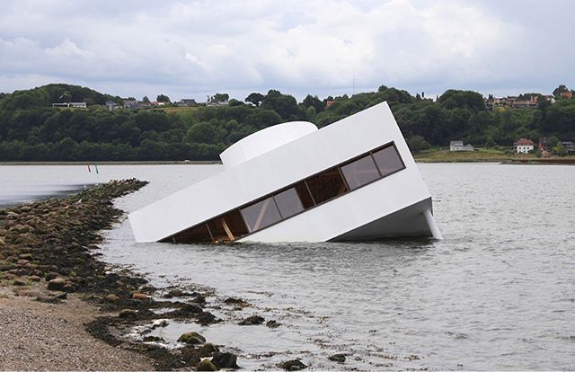 "Asmund Havsteen-Mikkelsen, Flooded Modernity (2018)  Villa Savoye has 'run aground' in Vejle Fjord, a comment on the state of modernity today. ""The geopolitical events of recent years – Brexit, the election of Trump, Putin's interference in democratic elections, the advancement of right-wing radicals in Europe – are happening with a background in and through the new digital media, which challenge modernity's classic notions of a critical public. A challenge through the formation of fake news, private information bubbles, and in dissolving the economic foundation of the traditional critical news media. The work Flooded Modernity is a critical commentary on the present, an attempt to draw attention to the importance of modernity and how we will deal with the legacy of modernity."" Asmund Havsteen-Mikkelsen  Images and text source:  http://www.asmundhavsteen.net/ http://www.vejlemuseerne.dk/exhibition/floating-art-2018  Flooded Modernity (2018) is part of 'Art and architecture below the surface' Floating Art 2018 by Vejle Art Museum @vejlekunstmuseum  Curator Pernille Rom Bruun  Floating Art involves a group of young and courageous artists and architects to reflect, build and construct their own time – and through an exploratory and knowledge-based practice, they exhibit all that takes place between the lines of the otherwise glossy surface.  For more information and to learn about the brilliant 'Floating Art' exhibition by Vejle Museum and the fascinating history of the area visit http://www.vejlemuseerne.dk/sites/default/files/katalog_floating_art_2018.pdf  #greatpublicart #architecture #publicart #contemporaryart #conceptualart #asmundhavsteenmikkelsen #floodedmodernity #floatingart #lecorbusier #vejlemuseerne #pernillerombruun #vejlefjord @asmundhavsteen"