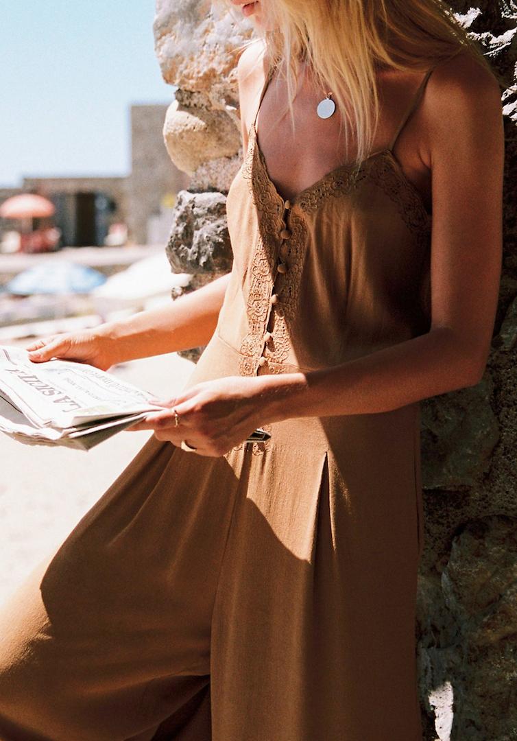 tan silk romper reading newspaper