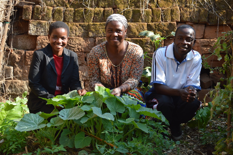 Face-to-Face Project Garden Facilitator, Emily Kayama, poses alongside husband and wife, Jessie and Shadreck Chindiwo, in their garden in Phunduma village, Malawi. August 2018