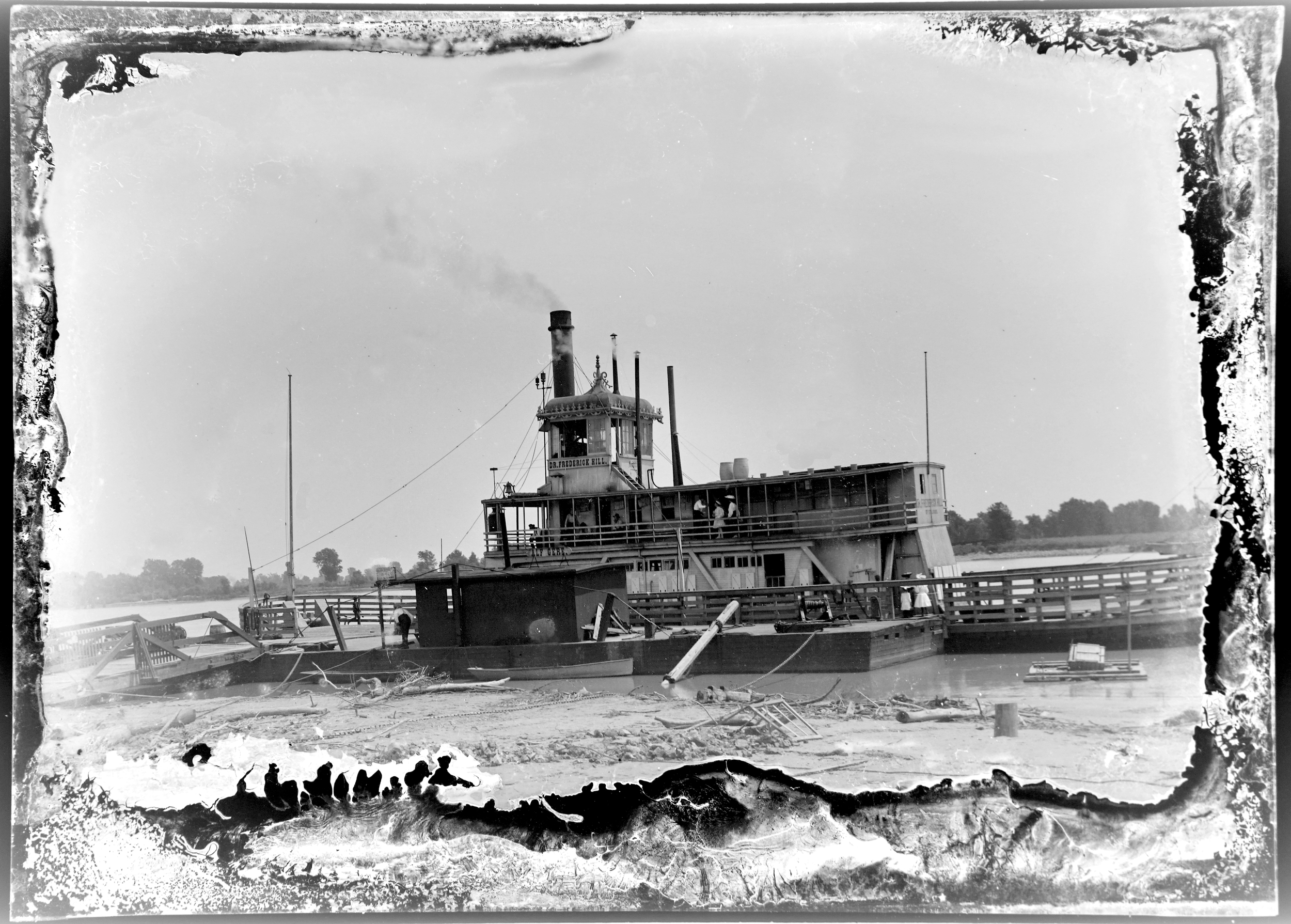 Glass plate photo of a not-so-grand riverboat, the hard-working kind used to transport goods like cotton and cattle.