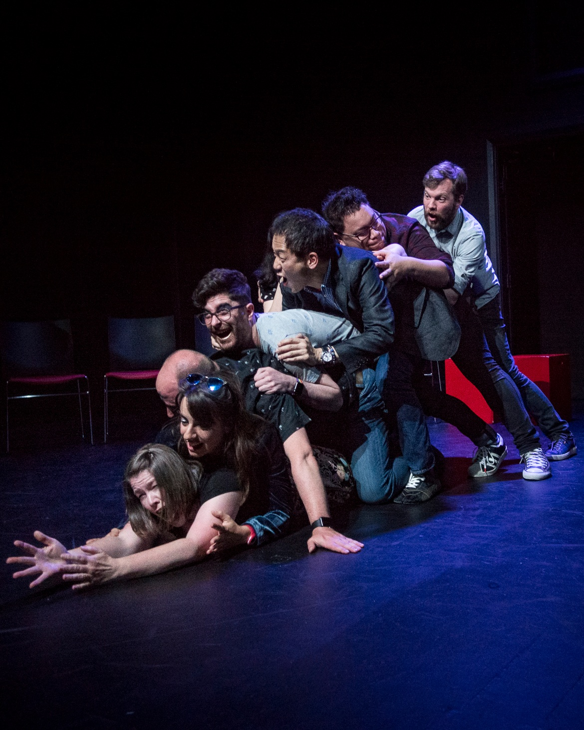 NZIF 2017 NZ vs the World Photo by Ali Little  Image: Seven improvisors piled on top of each other as if stuck down a chute, laughing and shrieking.